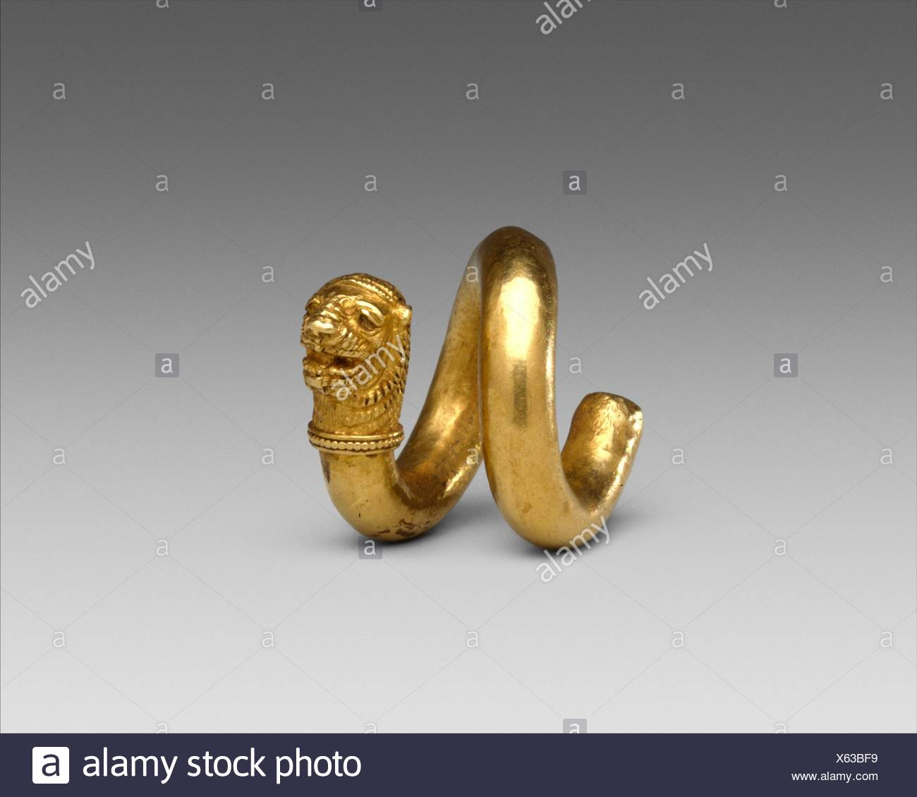 Gold and copper alloy spiral with lion-head terminal. Period: Classical; Date: 2nd half of the 5th century B.C; Culture: Cypriot; Medium: Gold, - Stock Image