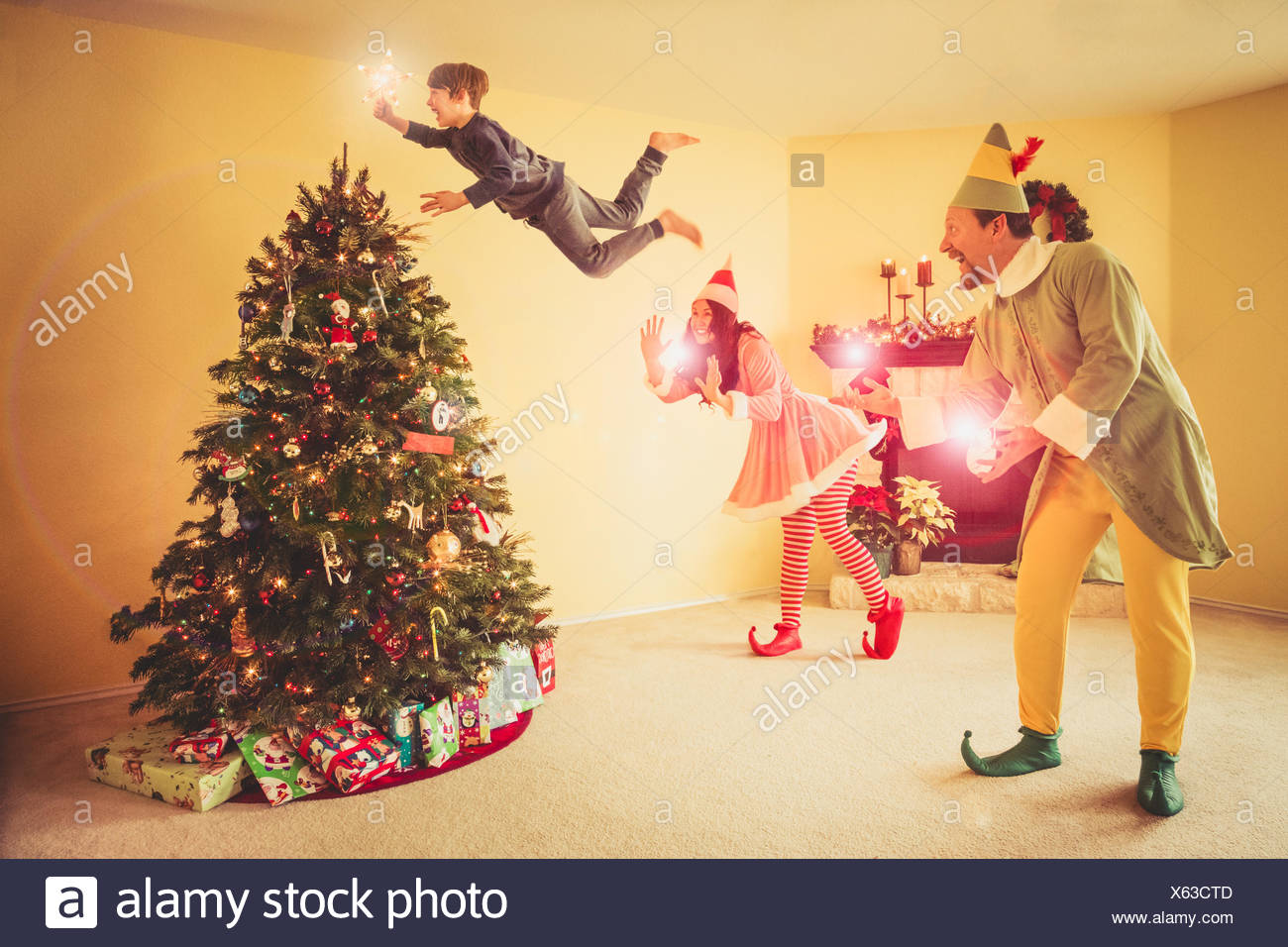Digital Composite Image Of Happy Family Decorating Christmas Tree At Home - Stock Image
