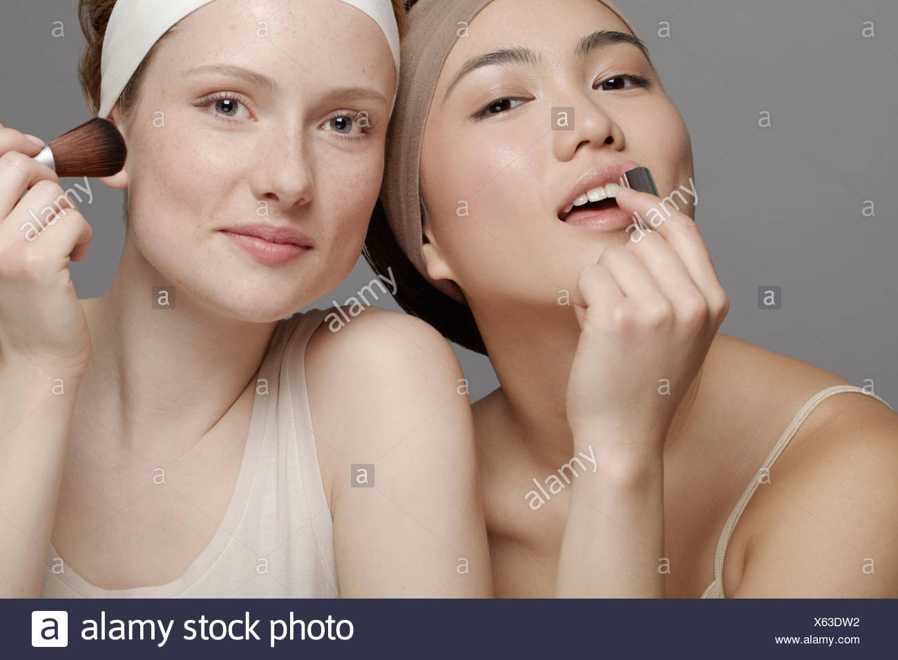 Young women putting on make up - Stock Image