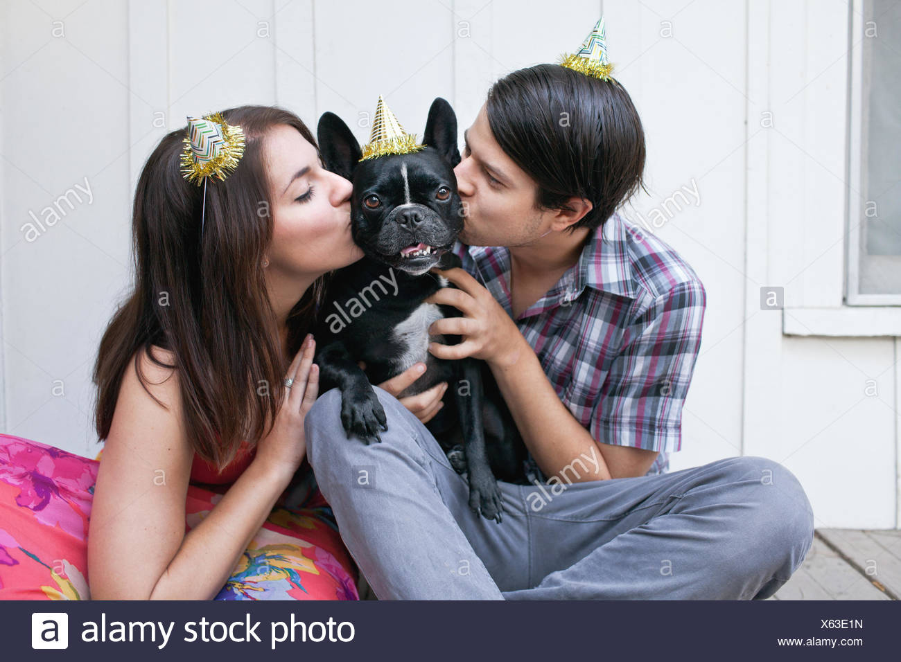 Young couple kissing dog on cheek and wearing party hats - Stock Image