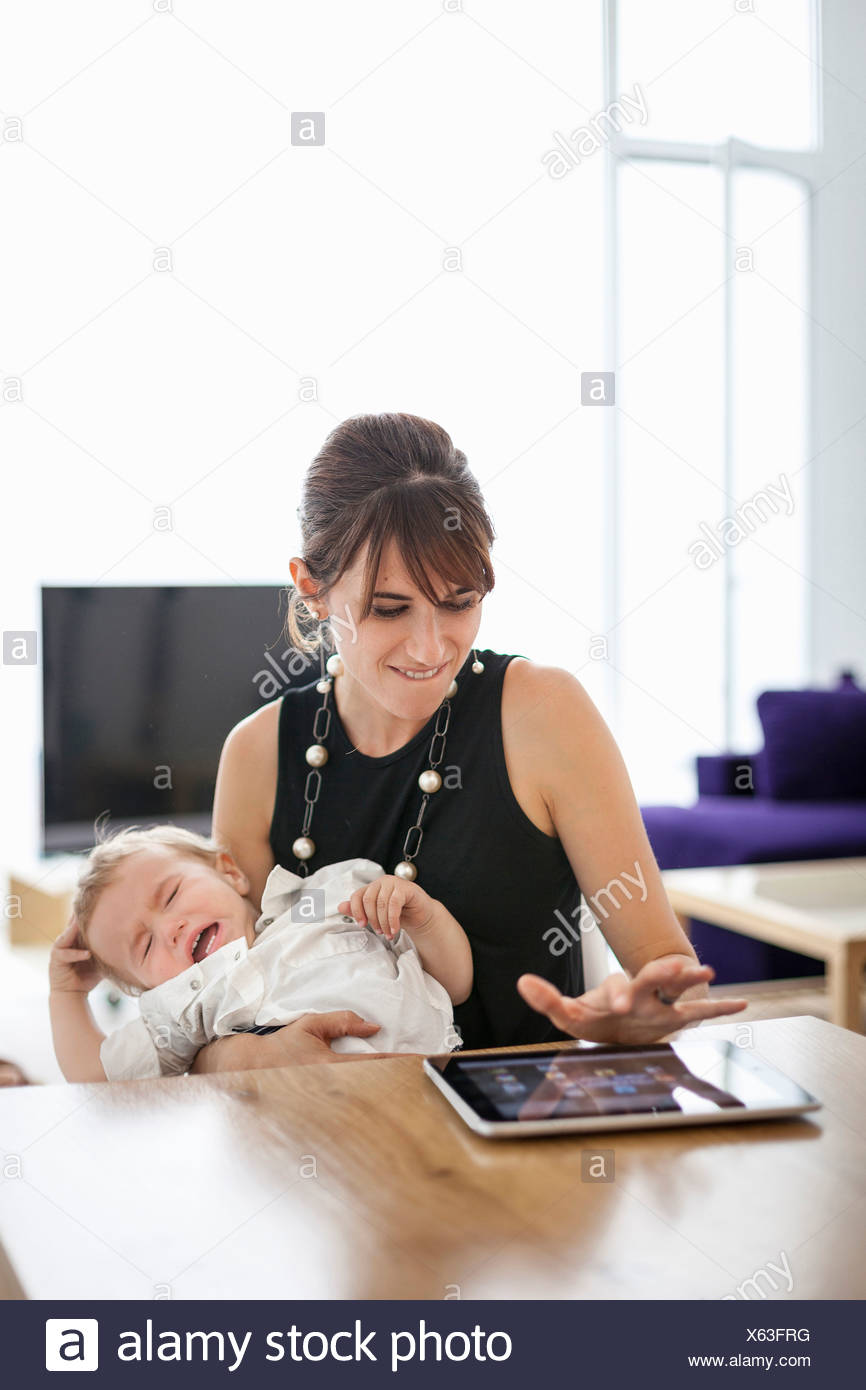 Businesswoman holding crying son - Stock Image