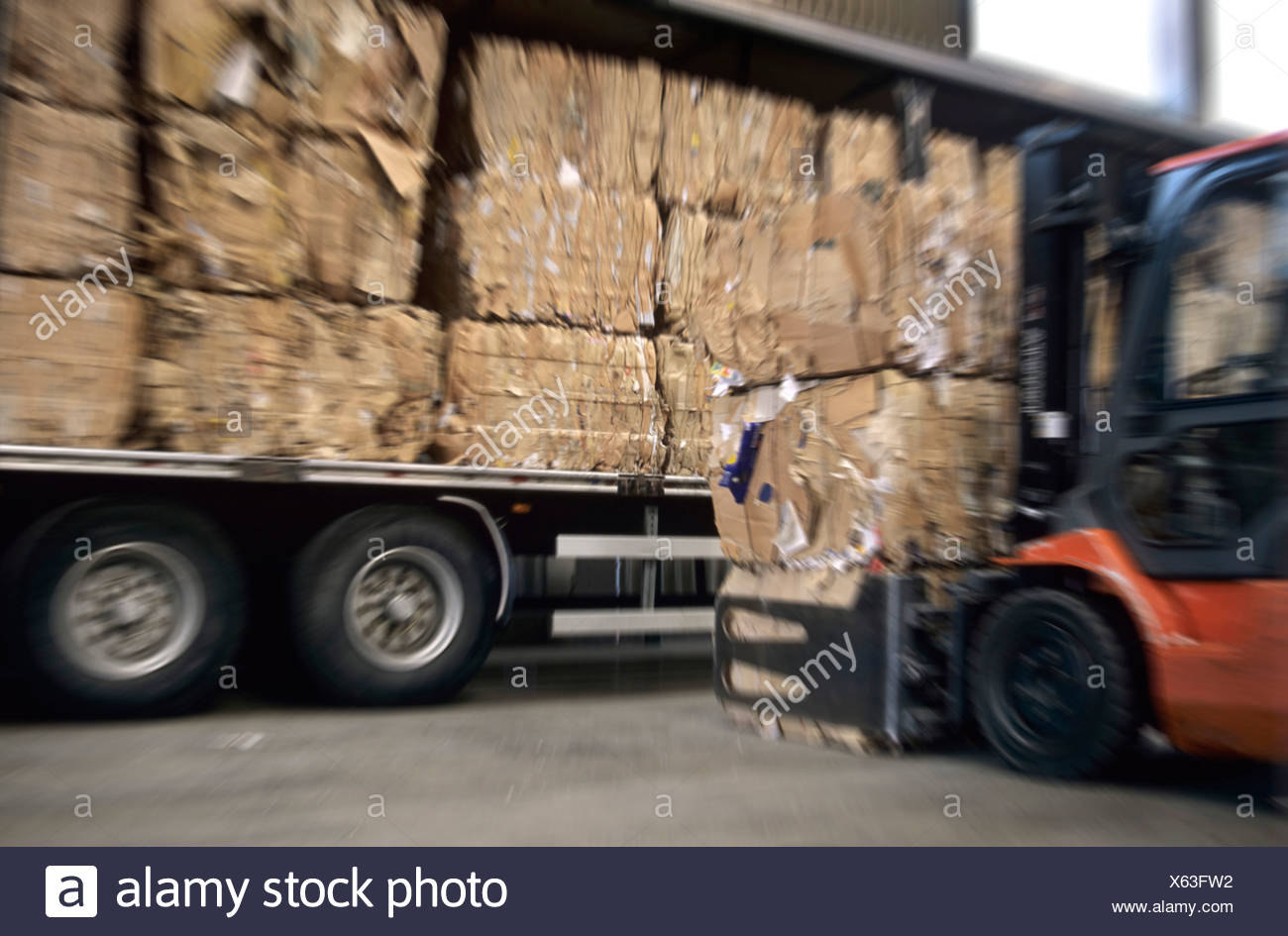 Forklift loading truck with cardboard bales, blurred Stock Photo