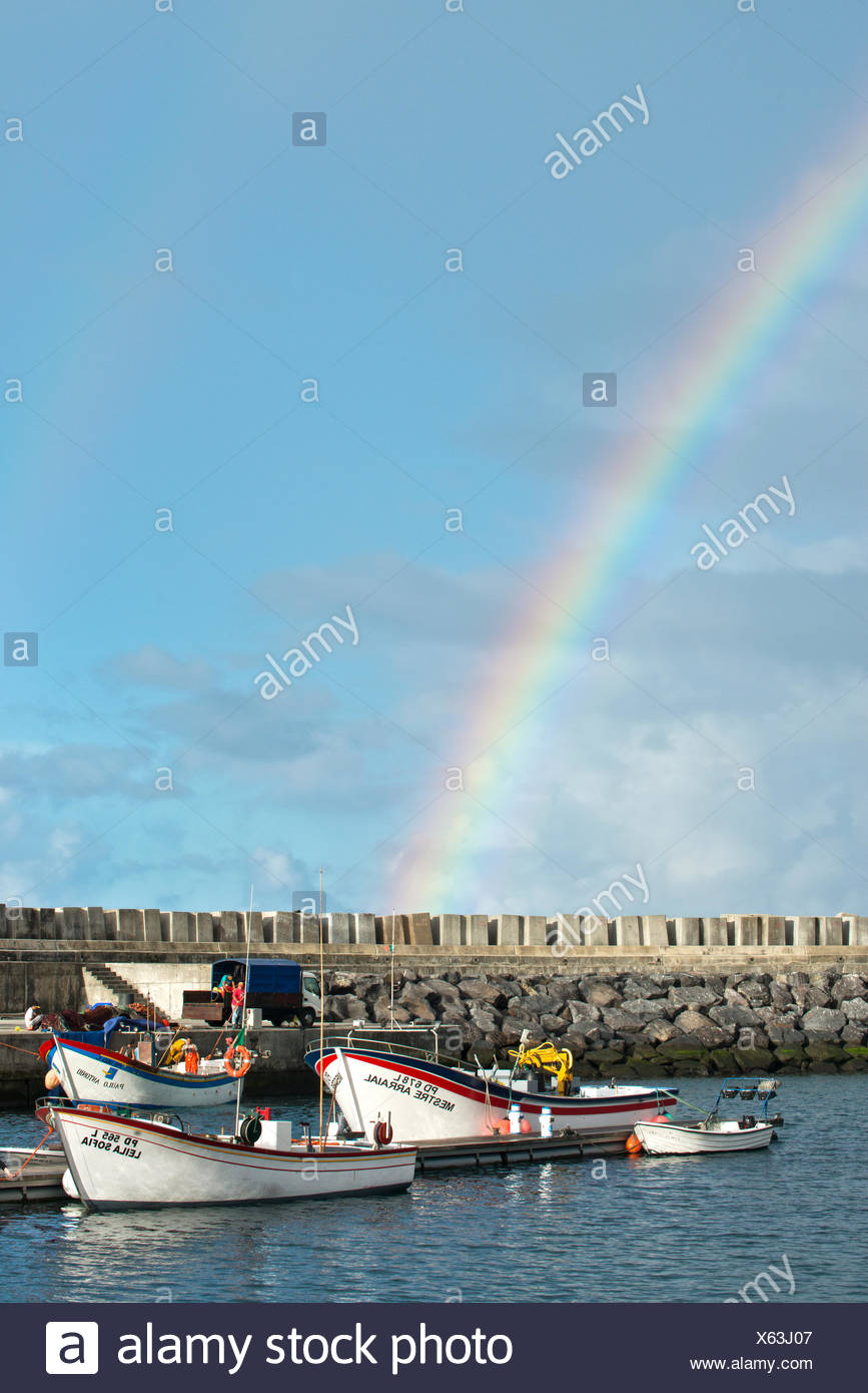 Rainbow bathes the waterfront at Vila Franca do Campo with fishing boats at sunset. - Stock Image