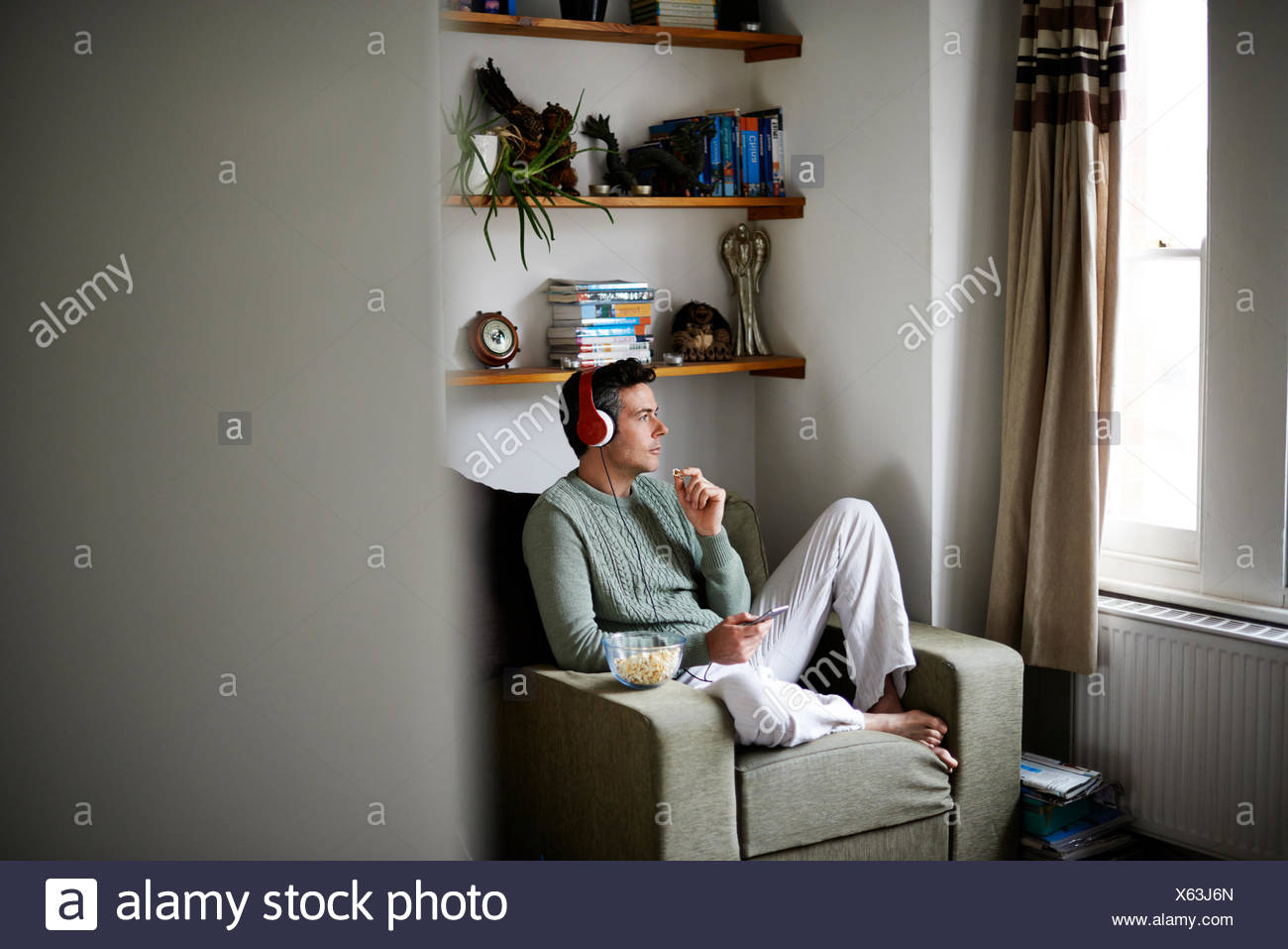 Man sitting in armchair with headphones looking through window - Stock Image