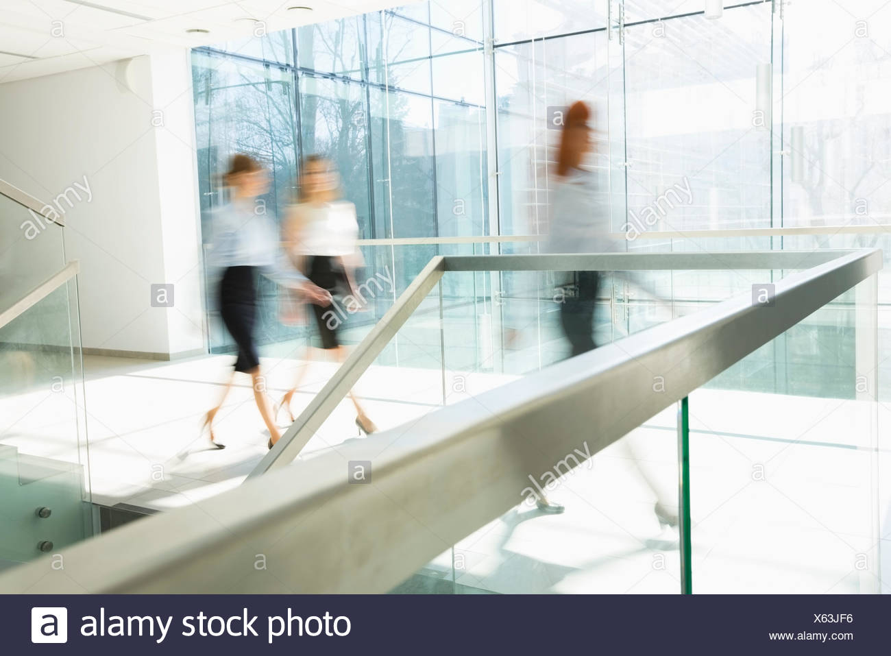 Blurred motion of businesswomen walking at office hallway - Stock Image