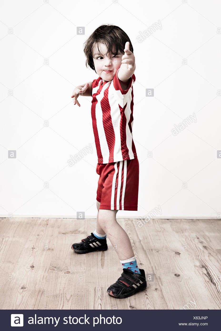 A boy in red and white striped shirt and football shorts standing pointing at the camera. - Stock Image