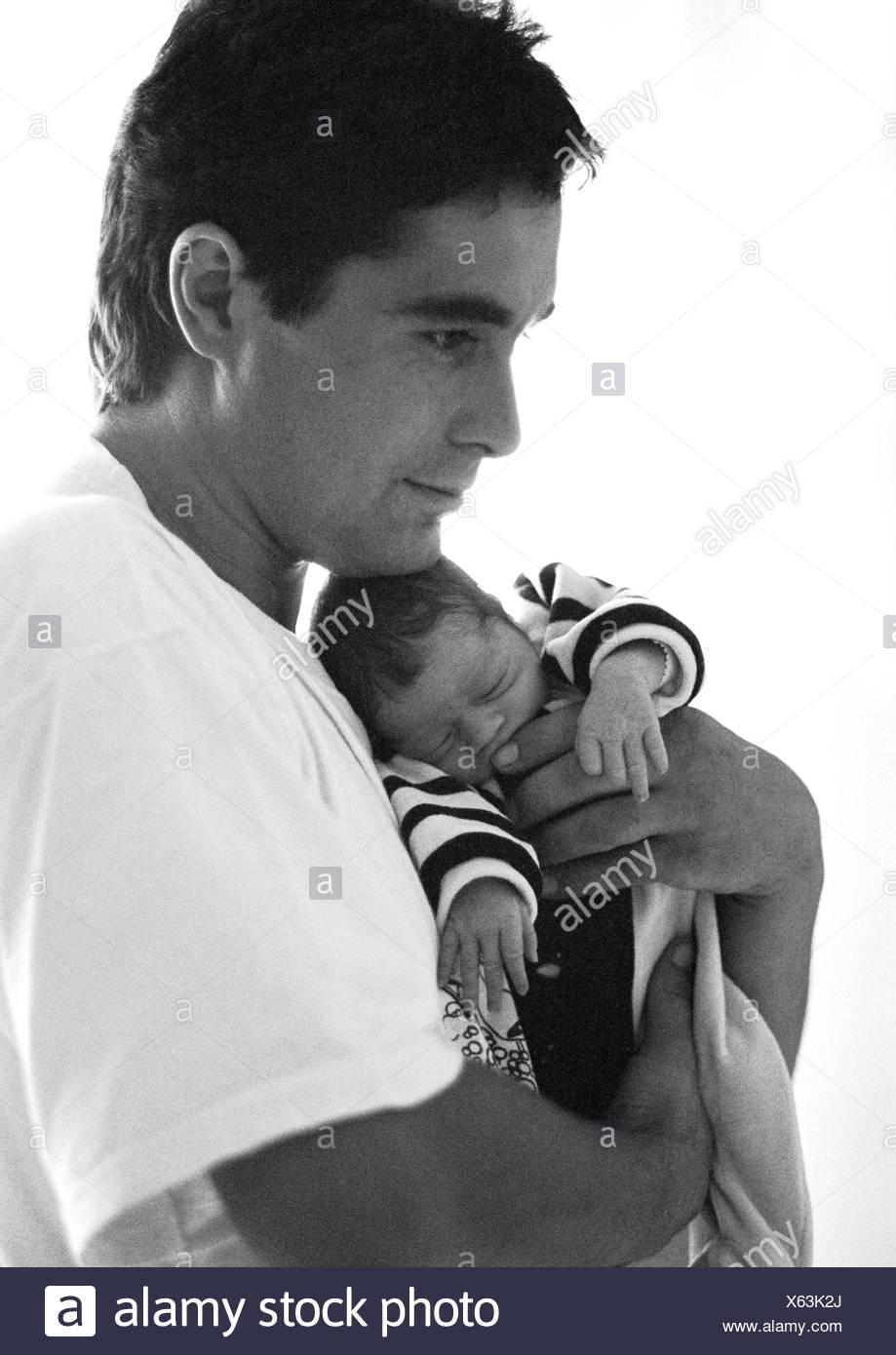 Man hugging baby, side view, b&w - Stock Image