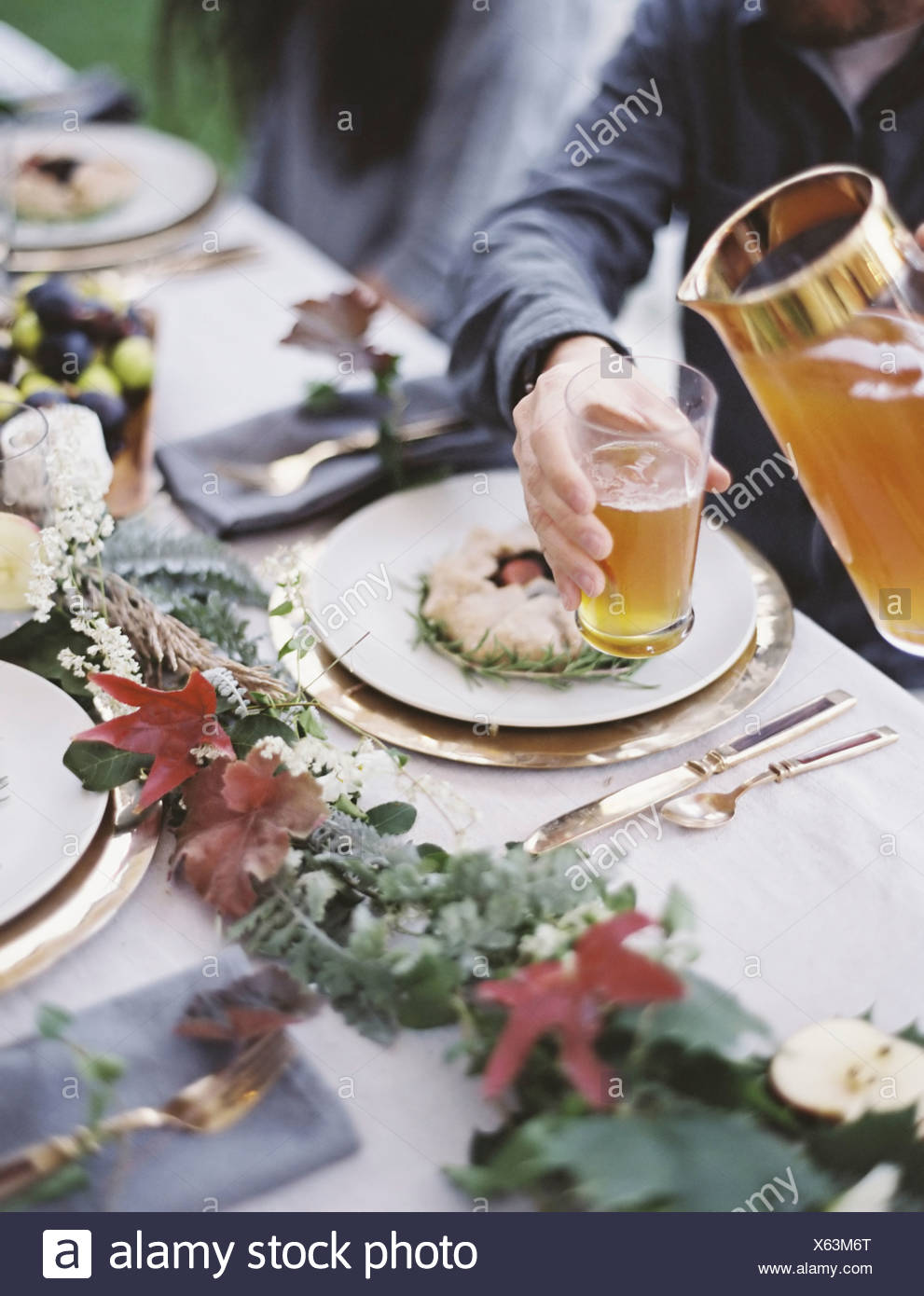 A celebration meal with table settings and leafy decorations A person pouring drinks into glasses - Stock Image