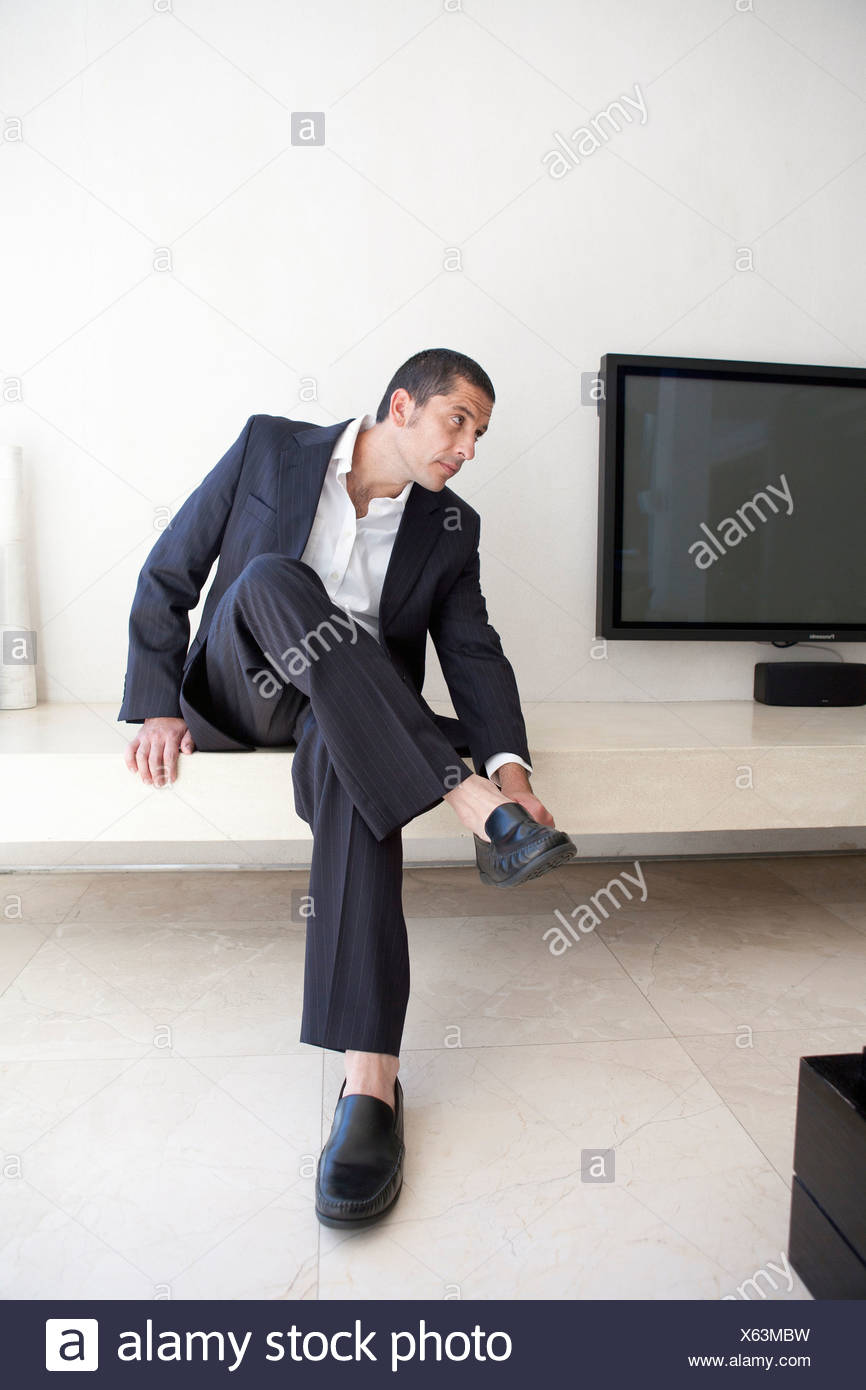 Businessman putting on shoes - Stock Image