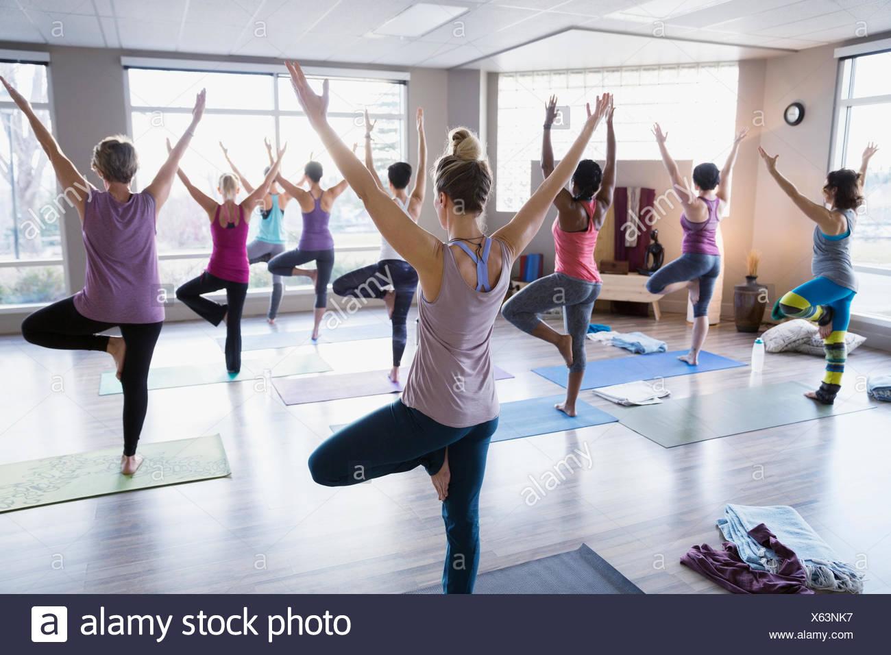 Women practicing tree pose in yoga class Stock Photo