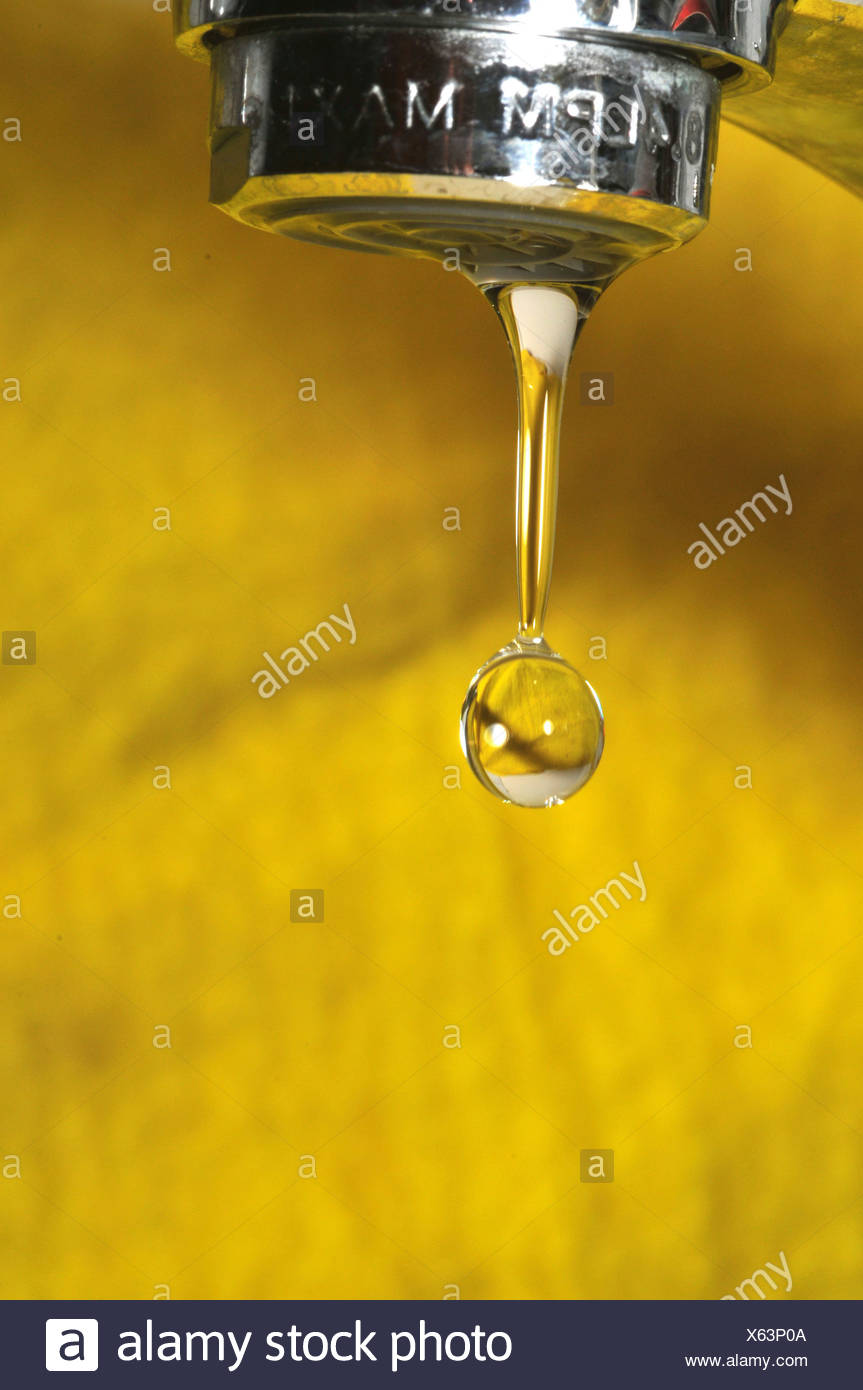 Water dripping from a tap on yellow background - Stock Image