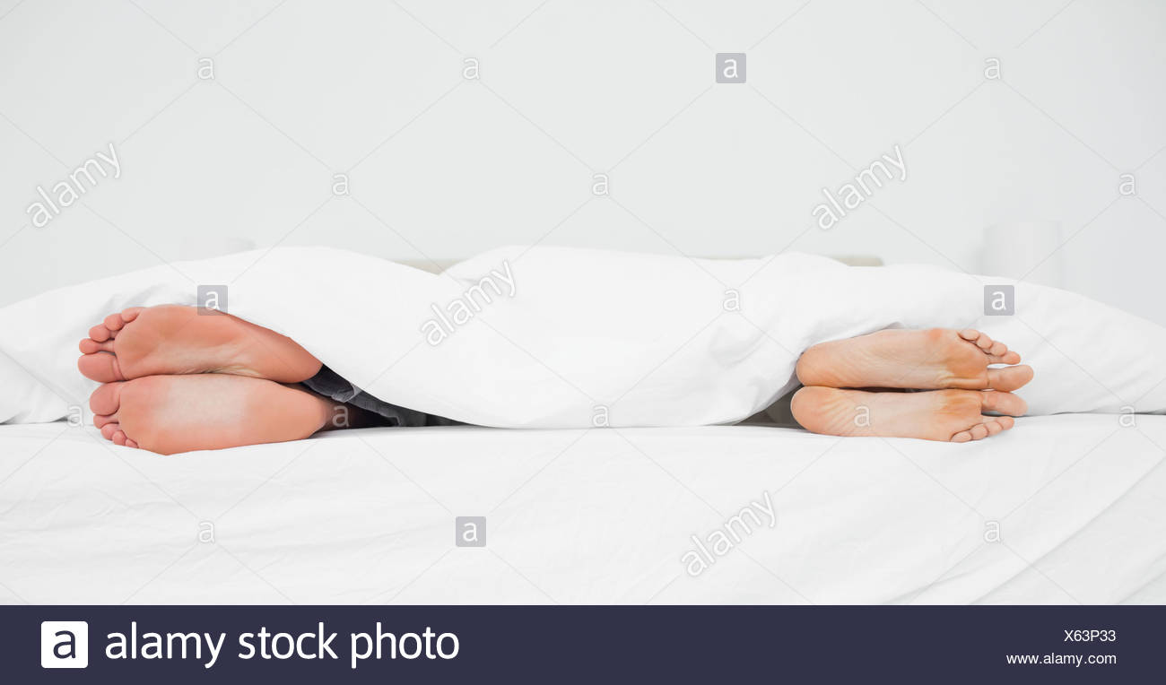 Man and woman's feet in a bed turned away from each other Stock Photo