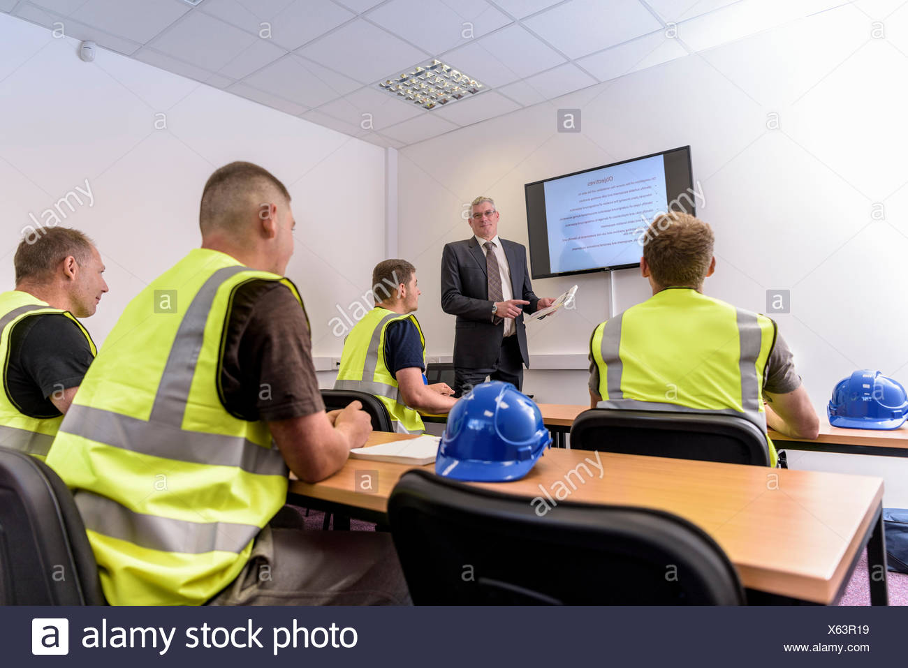 Apprentice builders in presentation in training facility - Stock Image