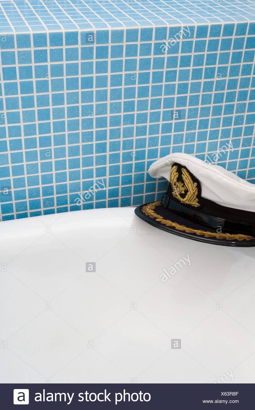Captain hat on edge of bath - Stock Image