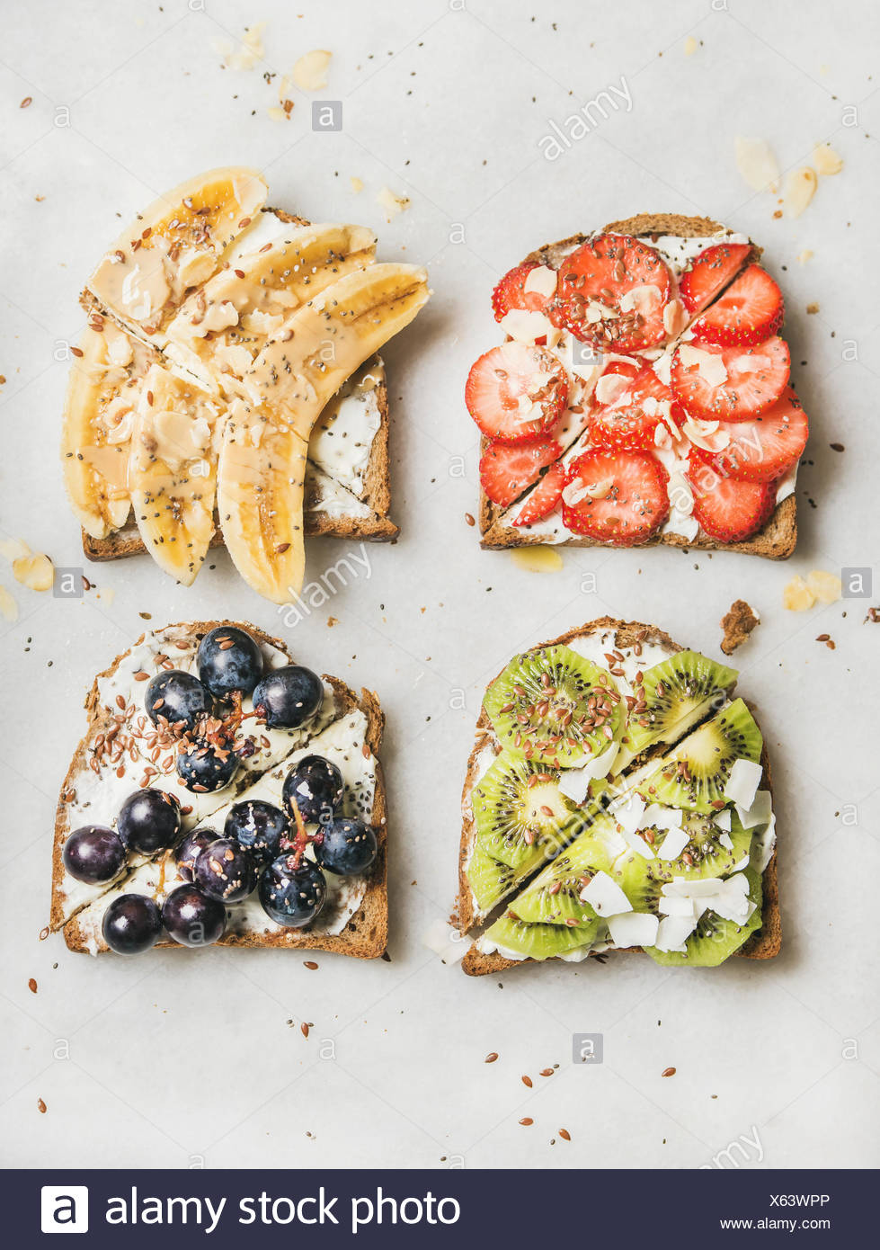 Healthy breakfast toasts. Wholegrain bread slices with cream cheese, various fruit, seeds and nuts. Top view, grey marble background Stock Photo