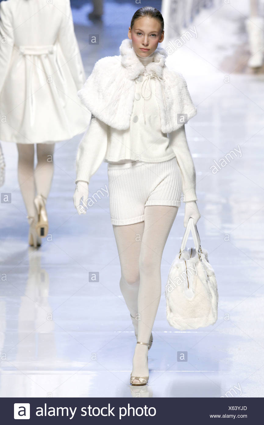 Blu Girl Milan Ready to Wear Autumn Winter Model wearing short white fur cape, white high necked jumper button details and - Stock Image