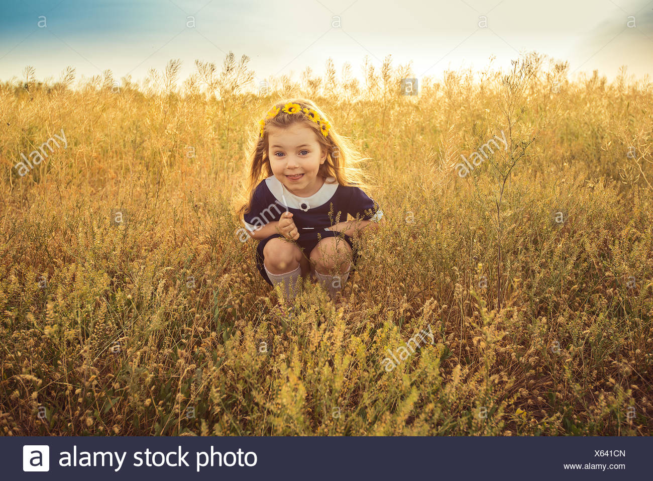 the beautiful little girl in a blue dress sitting Stock Photo
