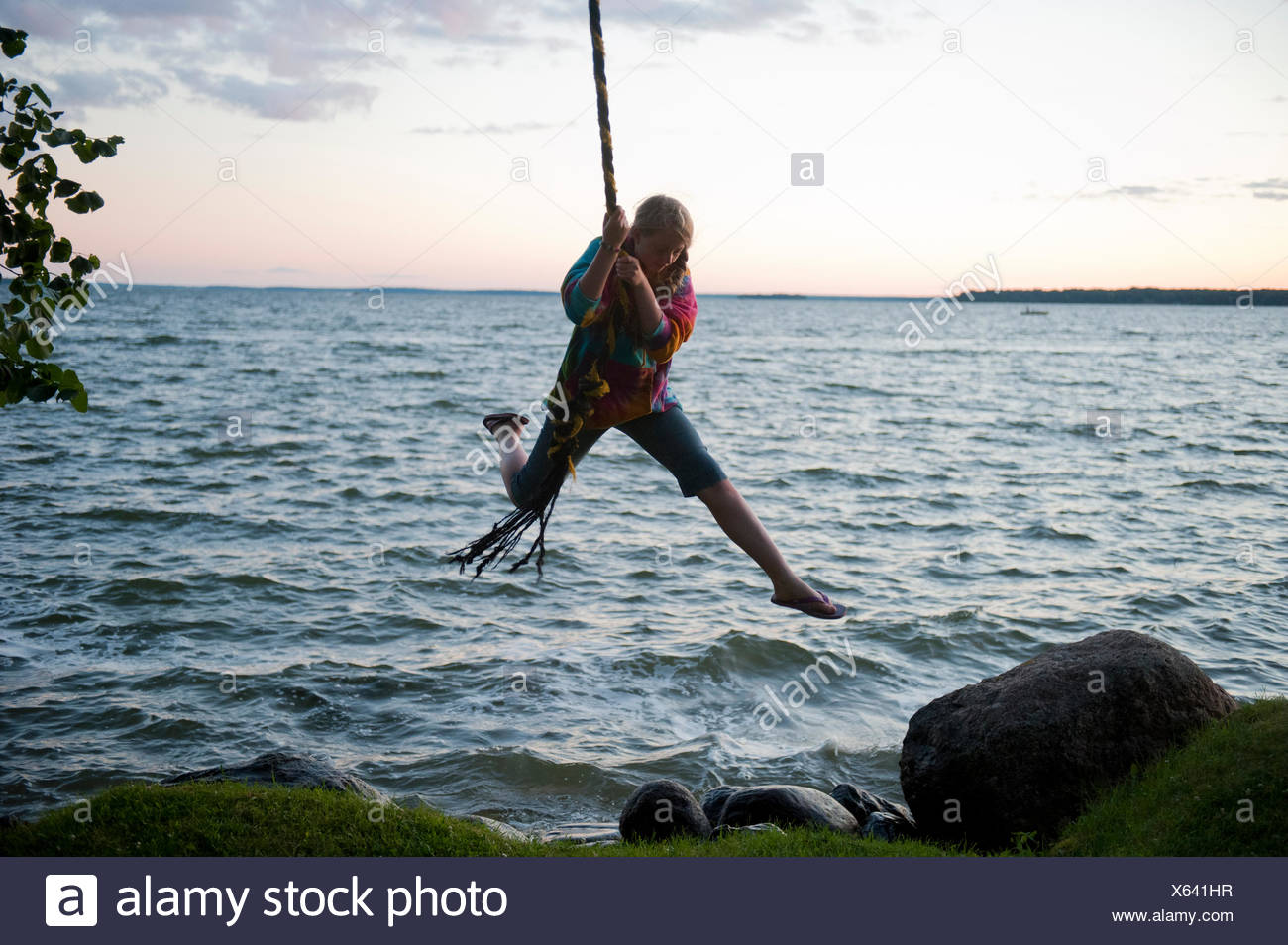 A teenage girl uses a rope to soar out over the water. - Stock Image