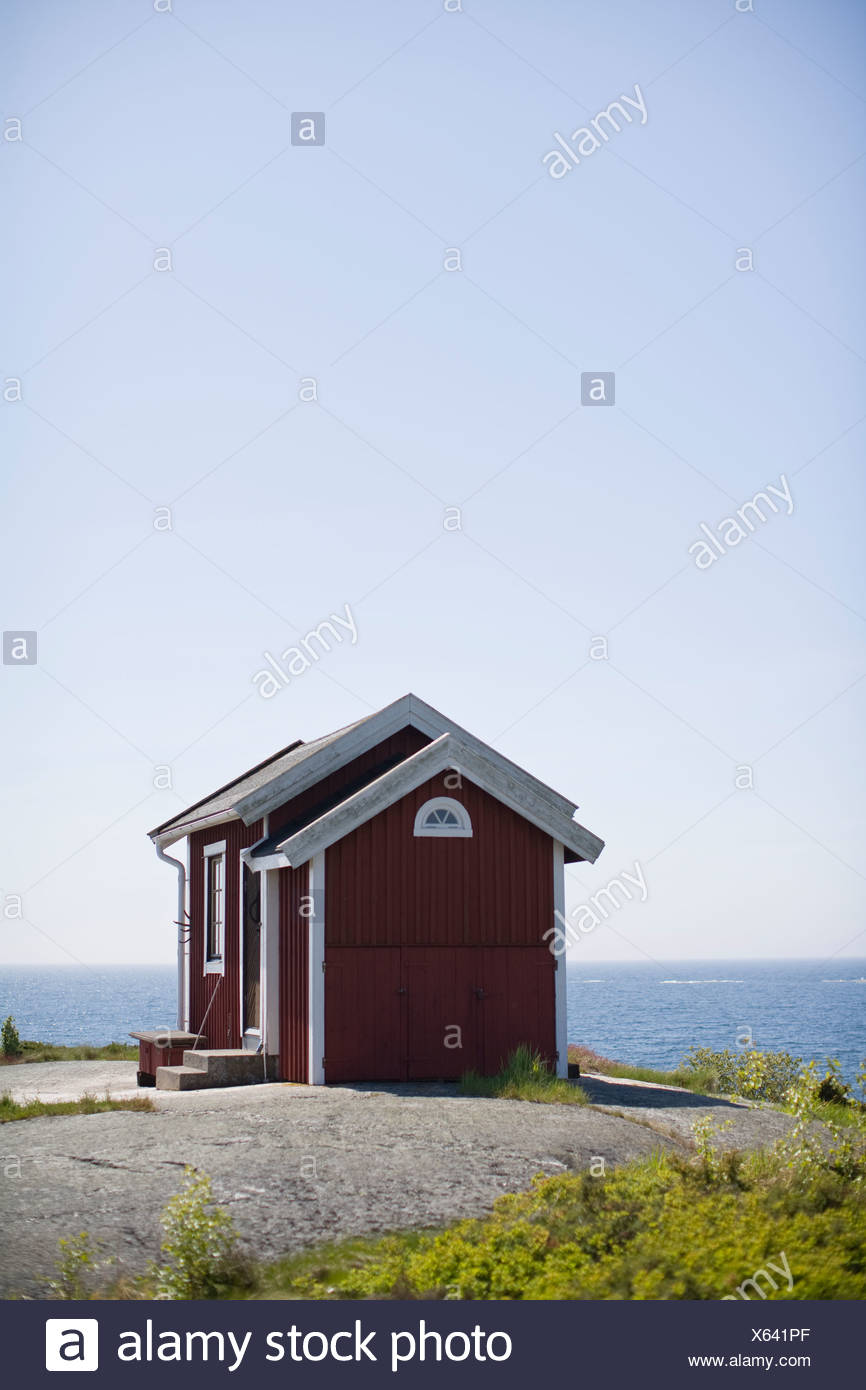 Cottages on rock next to sea - Stock Image