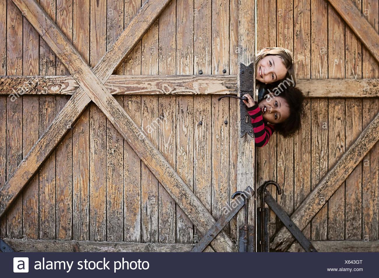 Two girls peeking round a wooden door - Stock Image