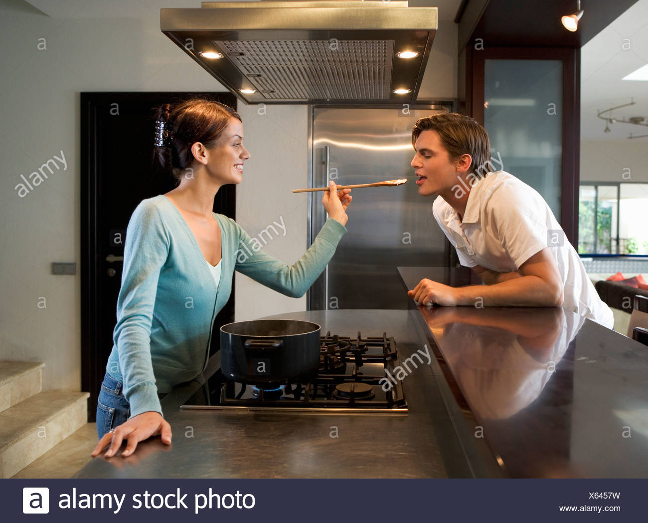 A young couple at home in their kitchen - Stock Image
