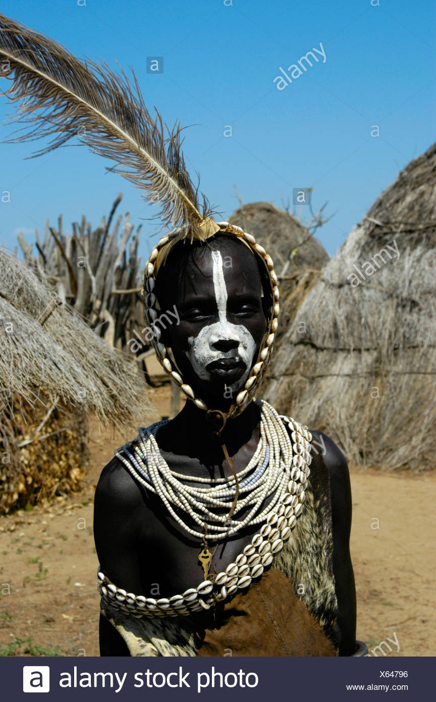 Young Karo tribesman wearing feathers in a headband and necklaces of Kauri Shells standing between straw huts, portrait, Kolcho - Stock Image