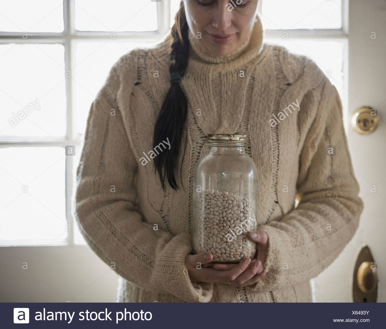 A woman in a cable knit sweater holding a glass jar of white beans - Stock Image