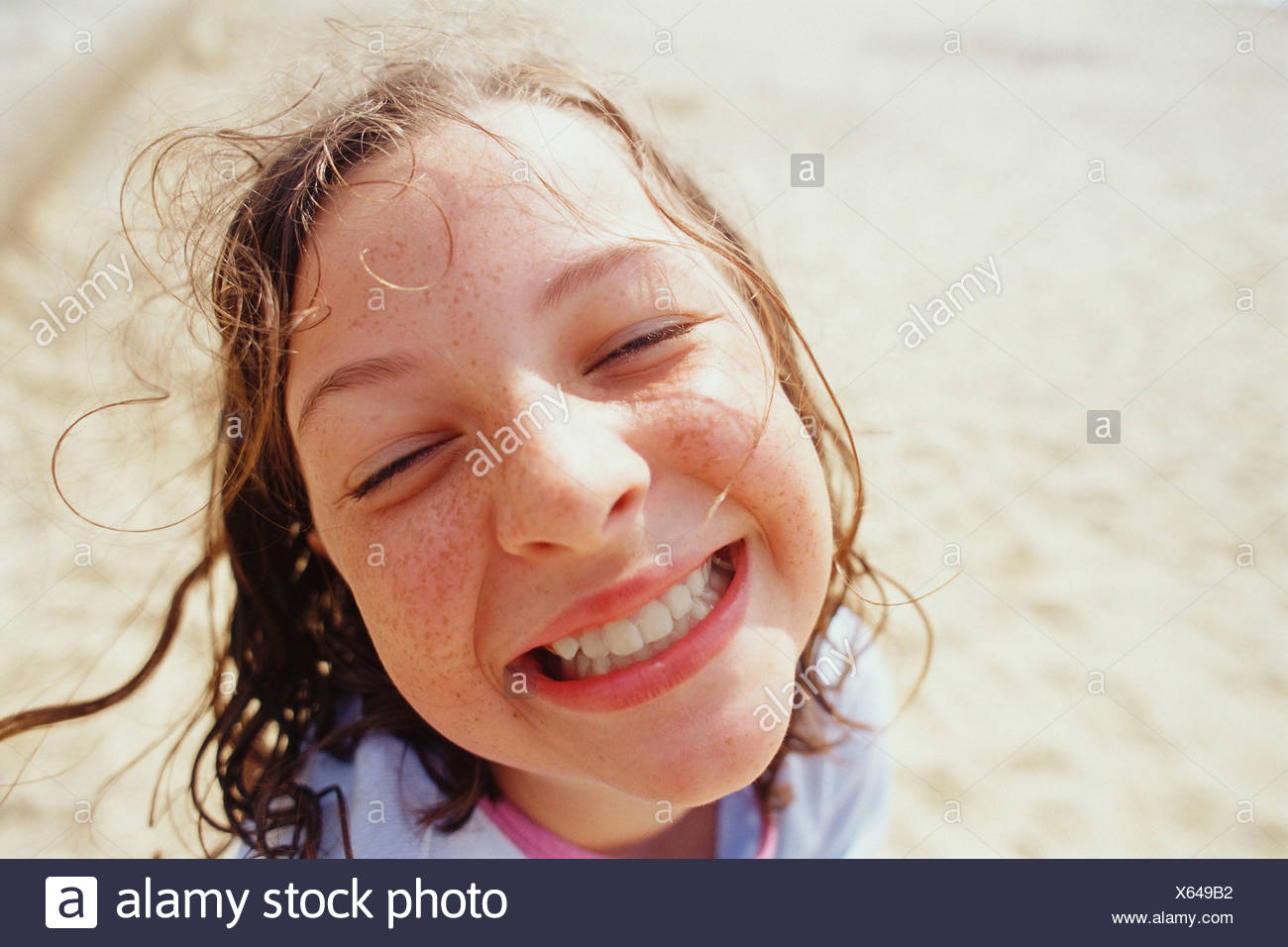 A young girl with a wide grin eyes half closed and wet hair outside in  rain. Stock Photo