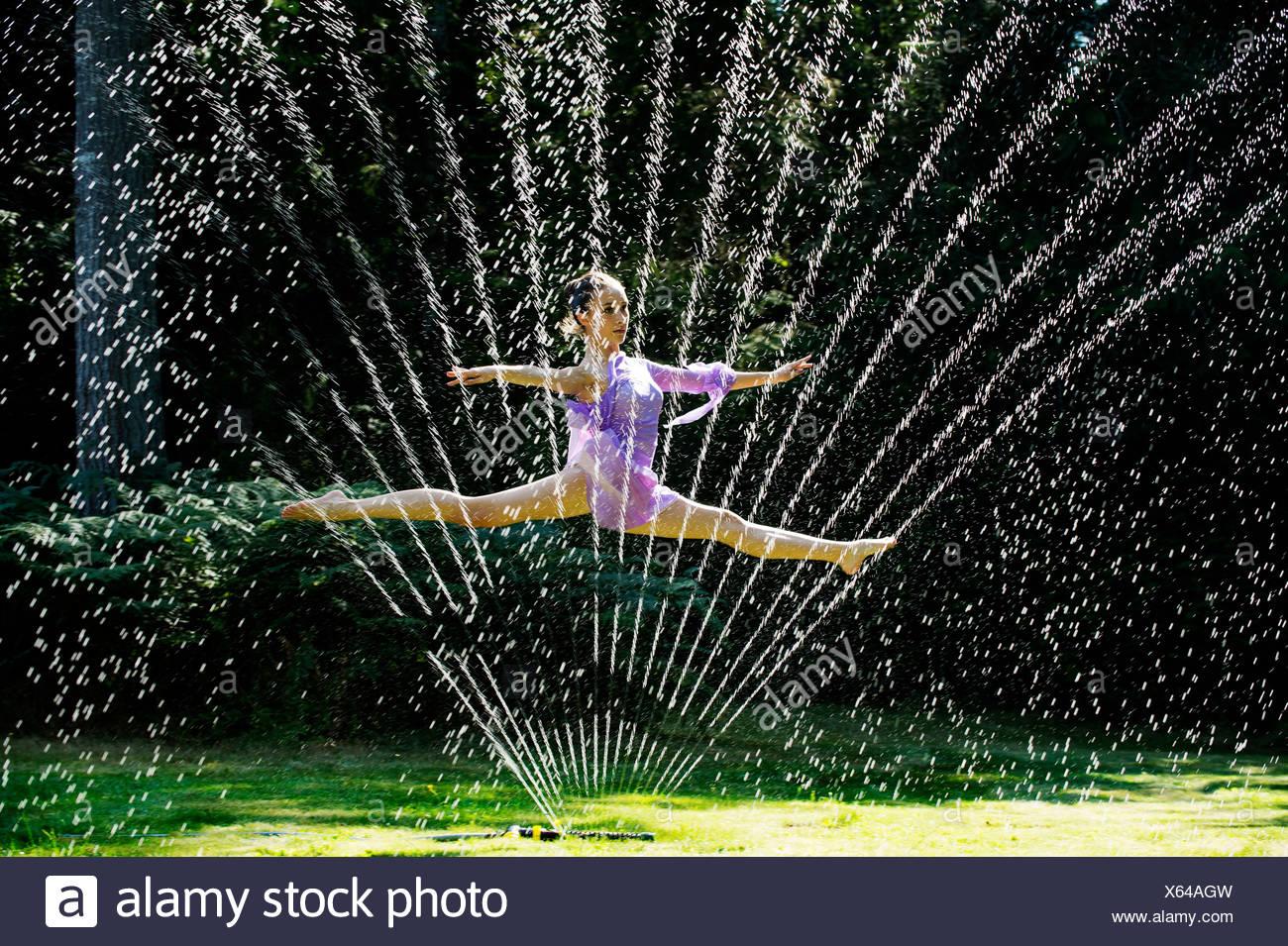 Ballerina leaping through a water sprinkler - Stock Image