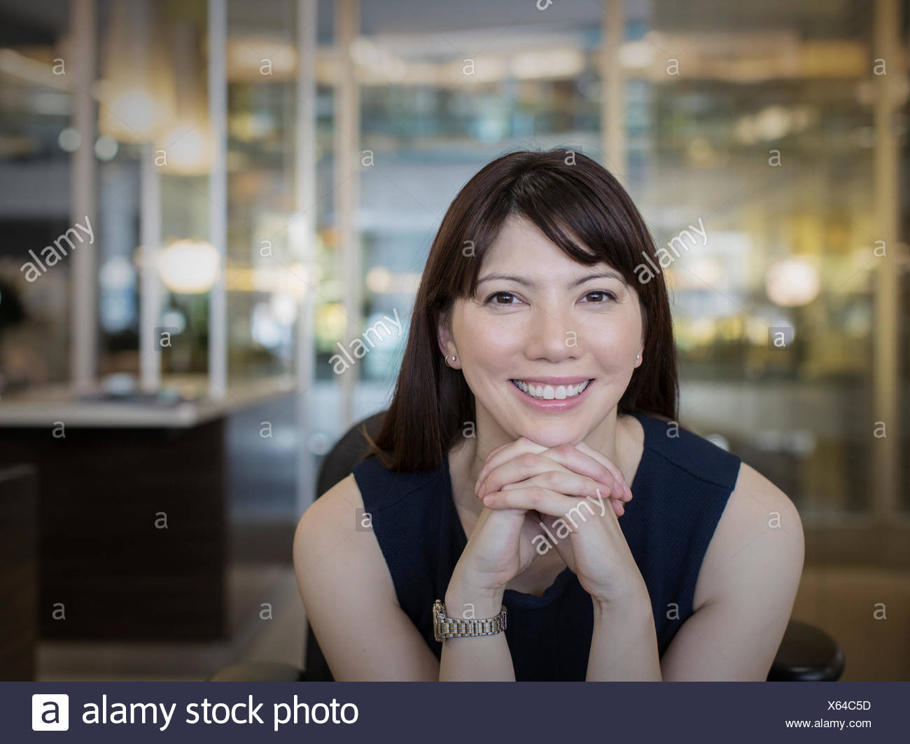 Portrait smiling businesswoman with hands clasped - Stock Image