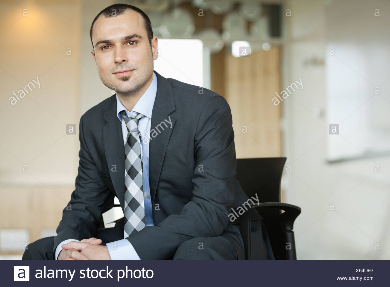 Portrait of confident businessman sitting on chair - Stock Image