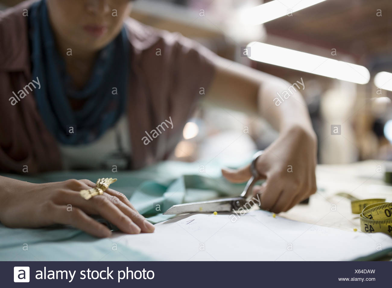 Female fashion designer cutting fabric with scissors - Stock Image
