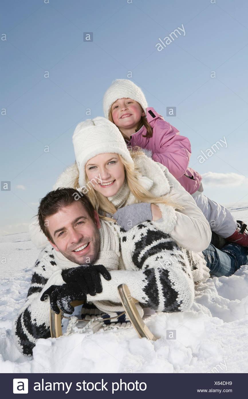 Germany, Bavaria, Munich, Family lying on sledge, smiling, portrait - Stock Image