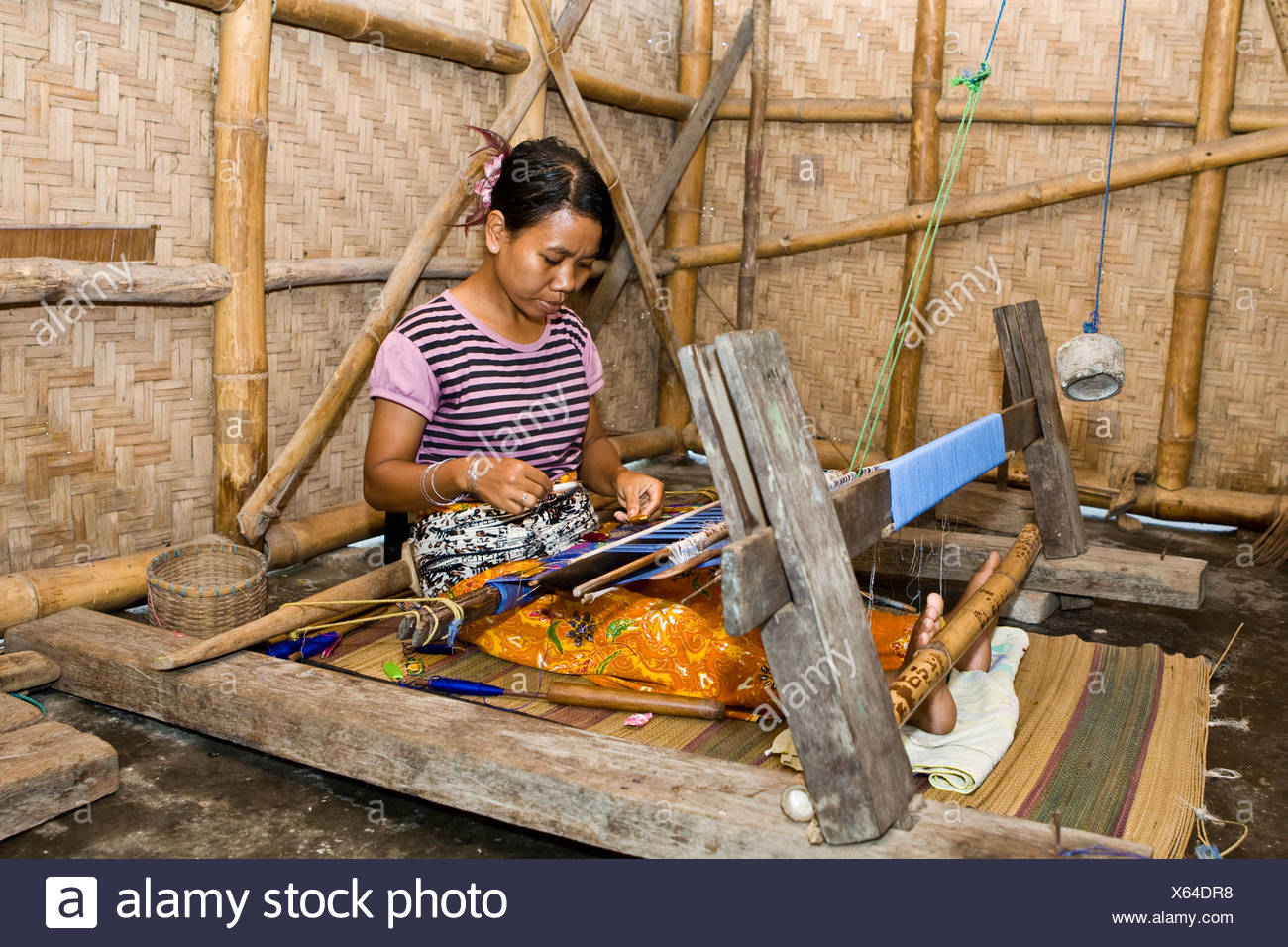 Woman weaving textiles in the traditional way at an old loom, Tete Batu, Lesser Sunda Islands, Indonesia, Asia - Stock Image