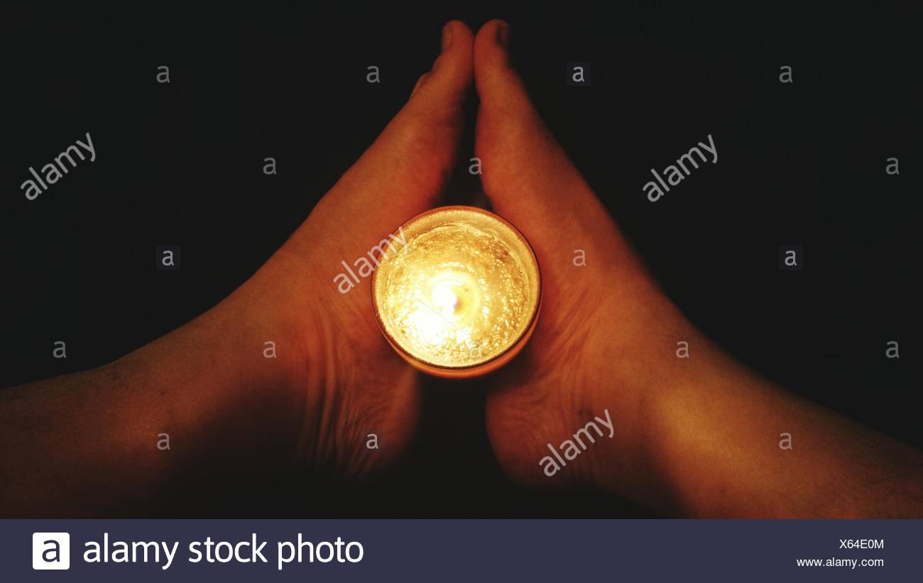 Close-Up Of Legs Holding Torch Over Black Background - Stock Image