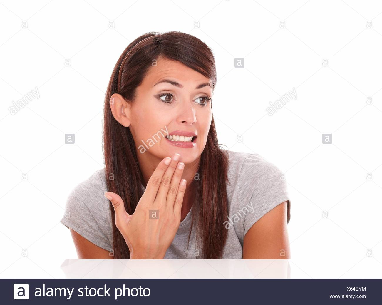 Headshot portrait of lovely latin woman with fail gesture looking to her right on isolated studio. - Stock Image