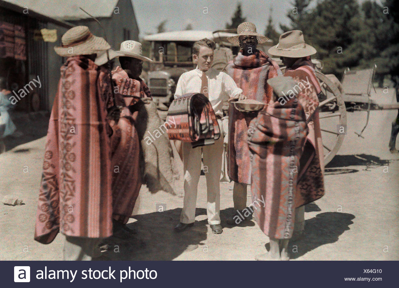 A business man swaps grain for blankets made by Basuto locals. - Stock Image