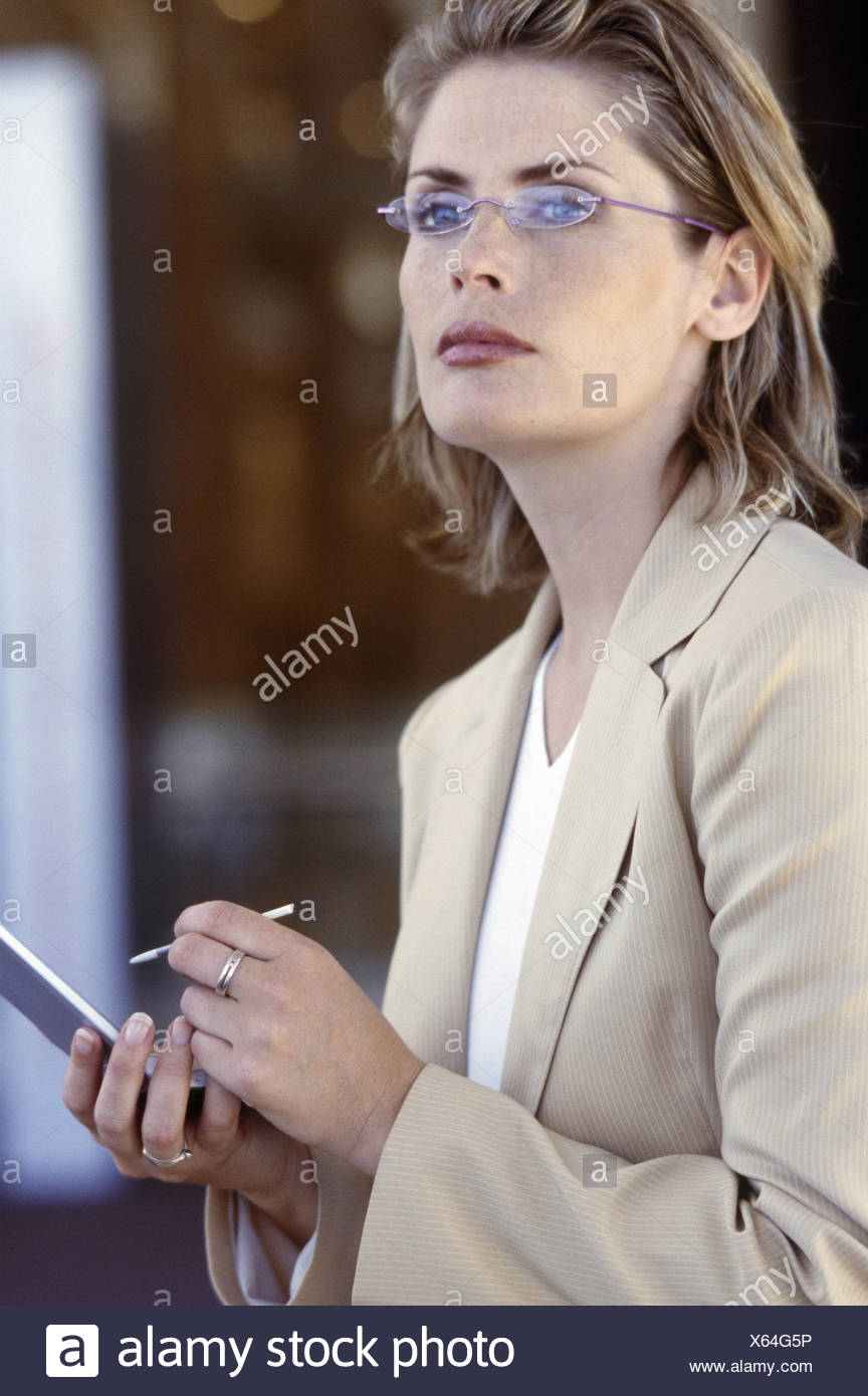 Woman using a PDA, looking up - Stock Image