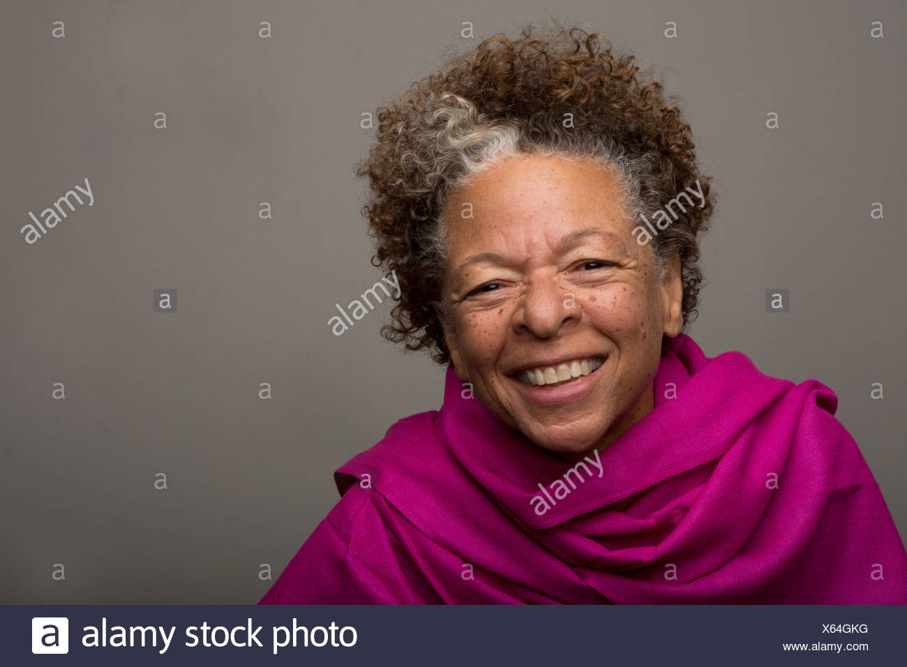 Studio portrait of happy senior woman in pink shawl - Stock Image