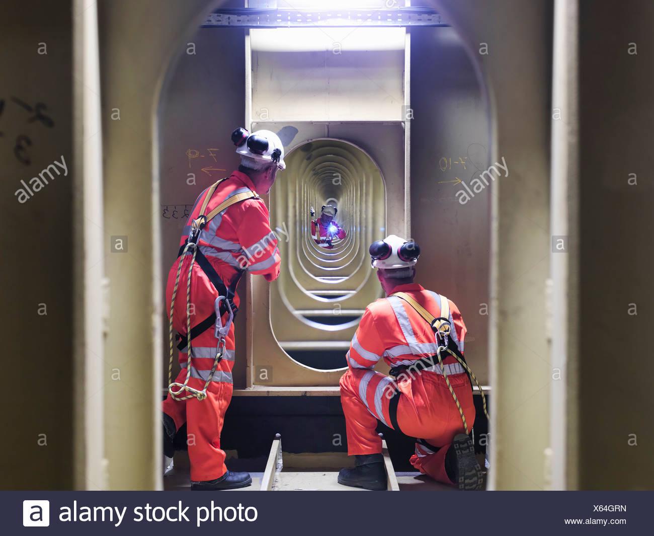 Civil engineers inspecting structure under carriageway of suspension bridge. The Humber Bridge, UK, built in 1981 - Stock Image