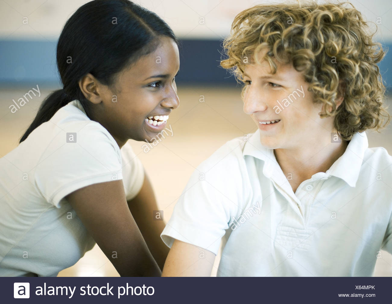 Teen couple smiling at each other - Stock Image