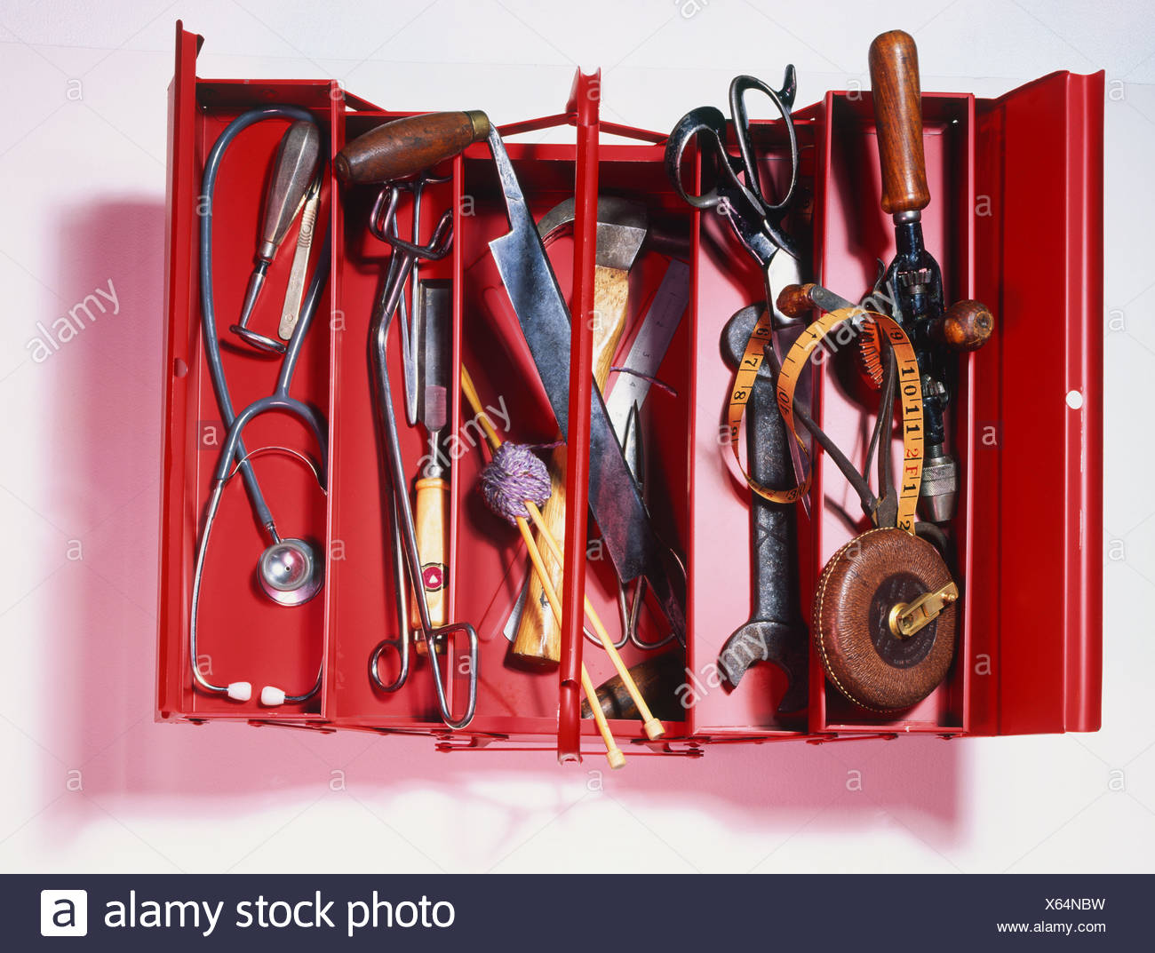 Red toolbox filled with assorted tools and other objects, opened out to show spanner - Stock Image