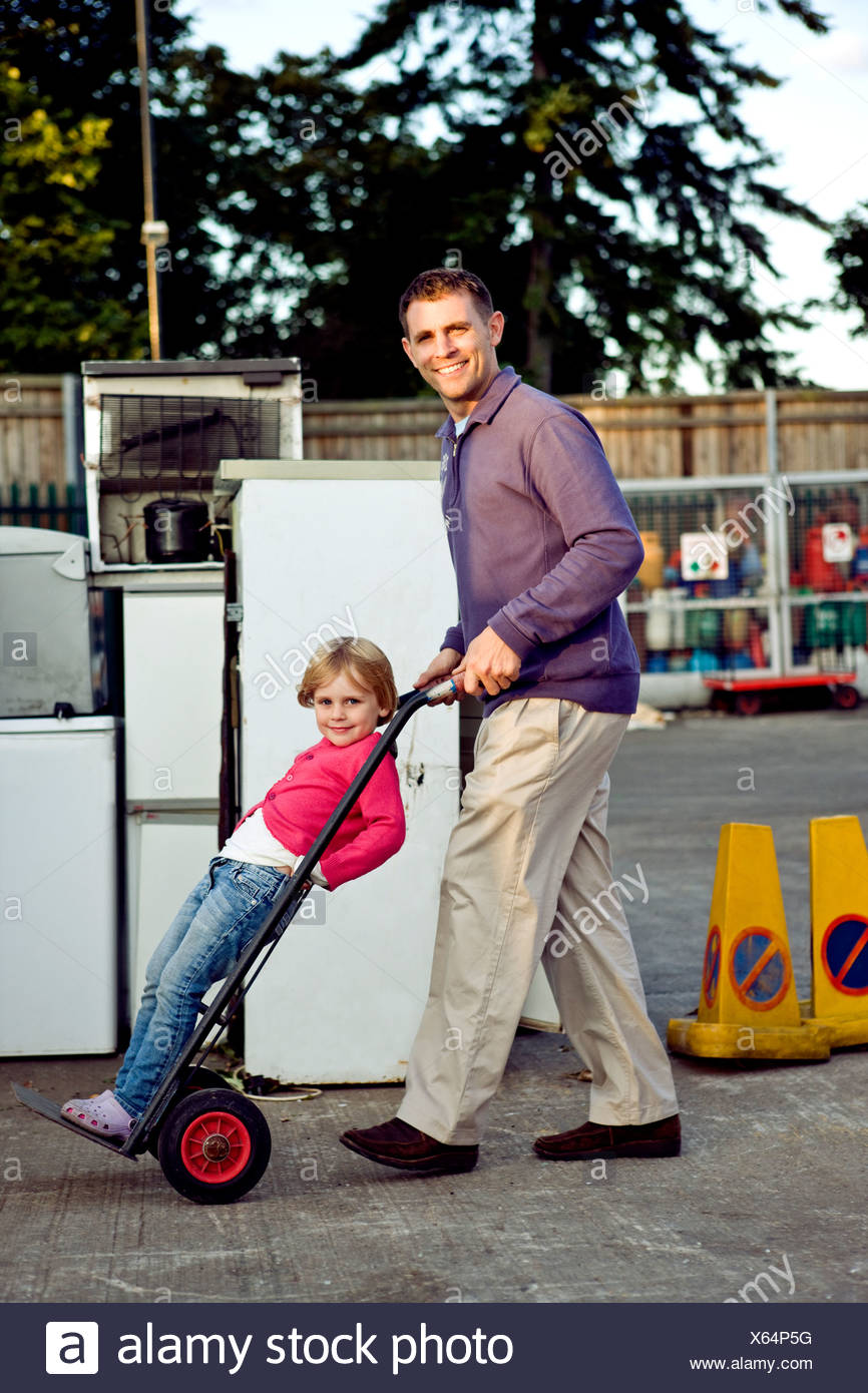 A father pushing his daughter on a trolley in a recycle center Stock Photo