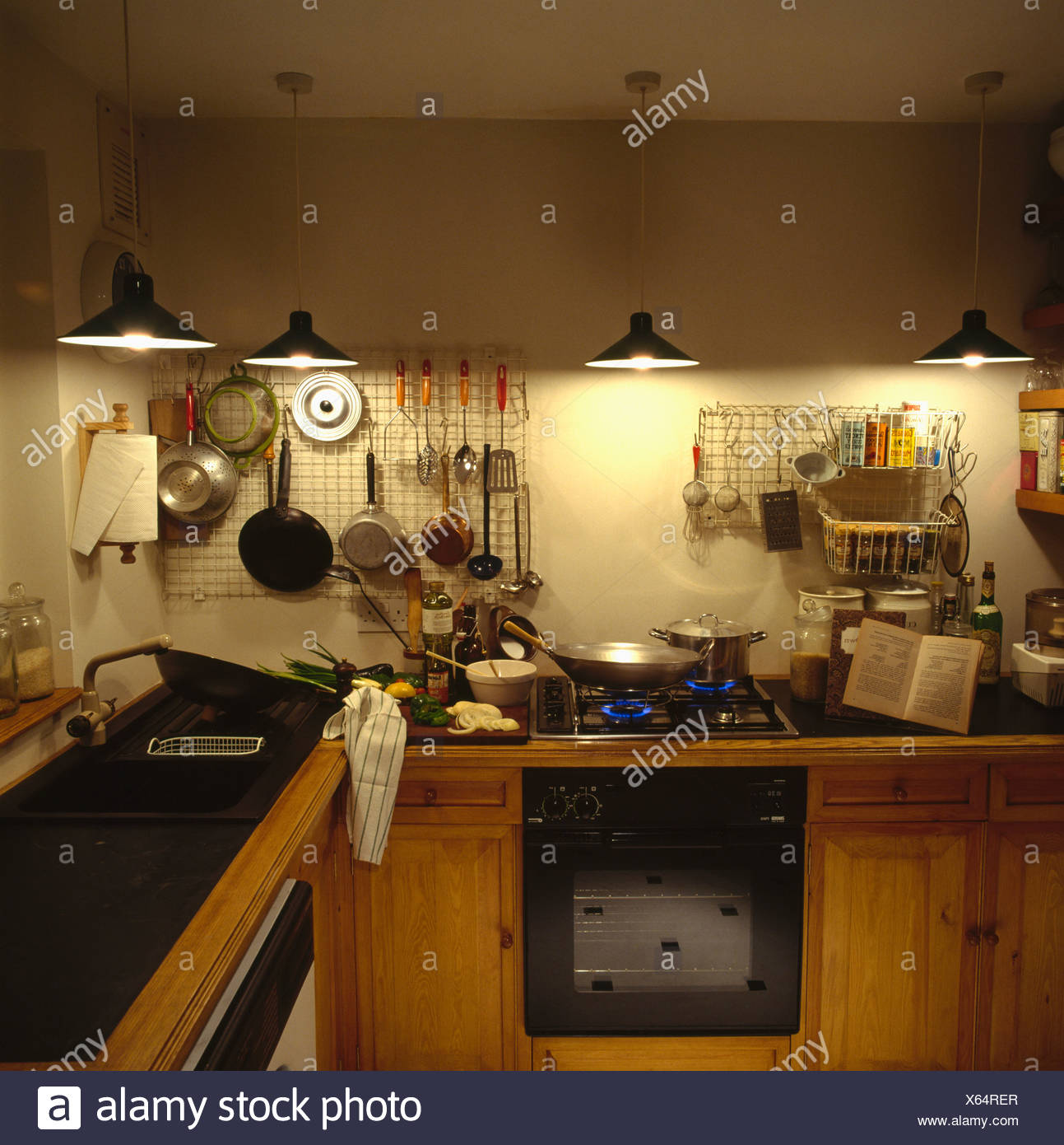 Pendant Lights Above Pans On Wire Wall Racks In Small Kitchen With Oven In Fitted Pine Units Stock Photo Alamy