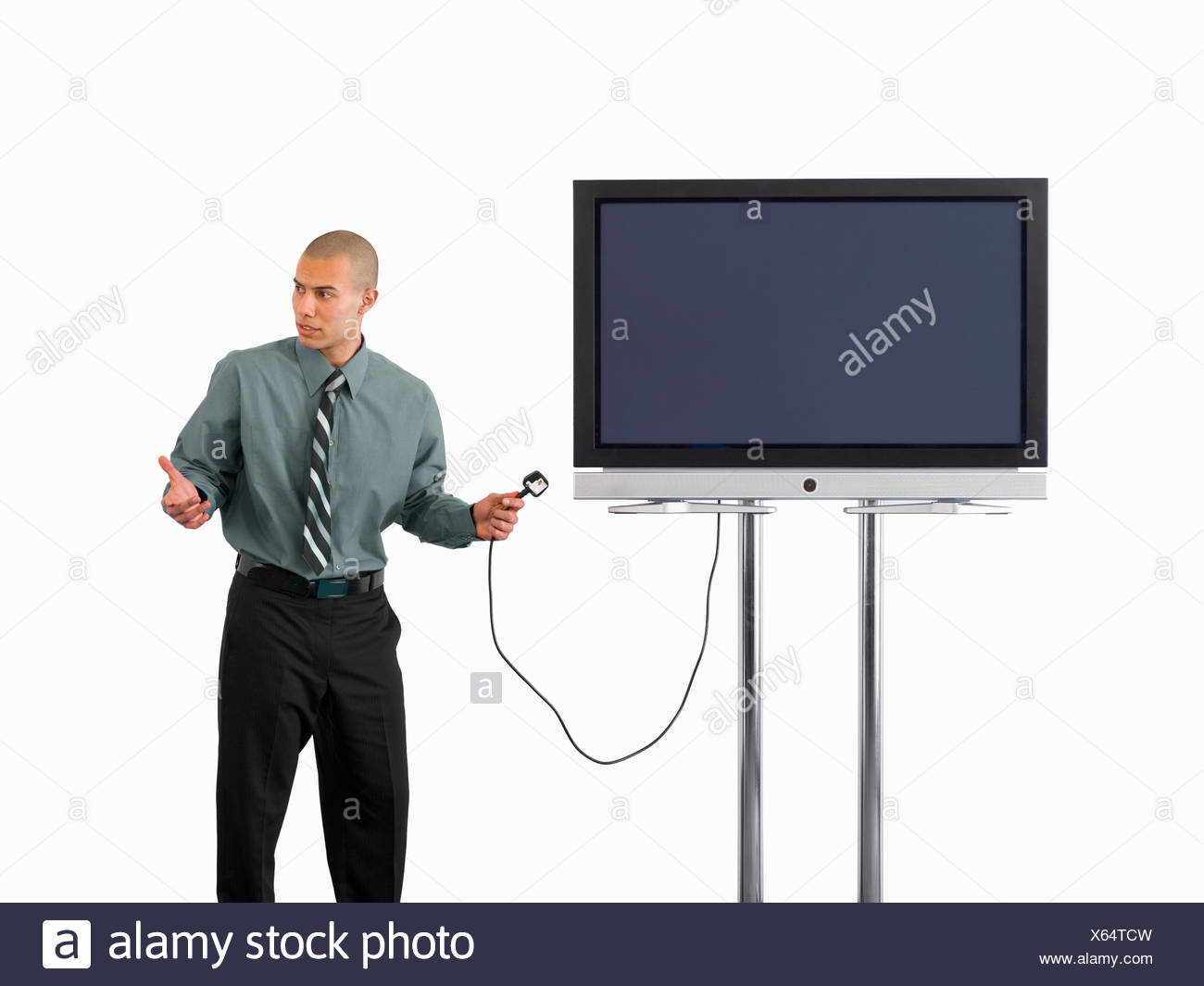 Businessman holding plug to widescreen television, cut out - Stock Image