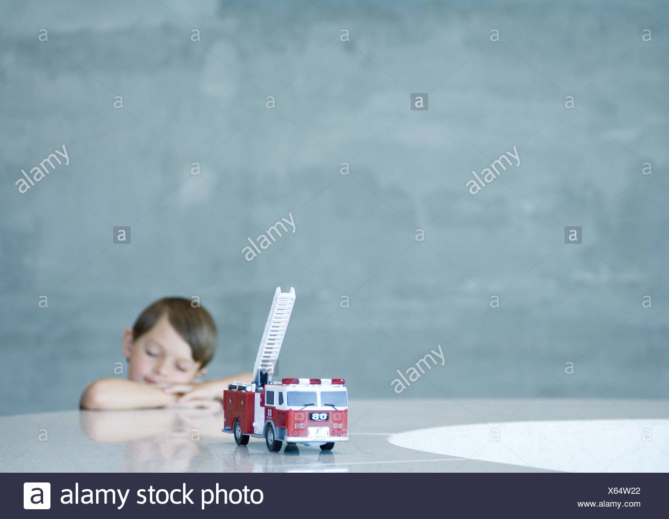 Boy dreaming behind toy firetruck - Stock Image