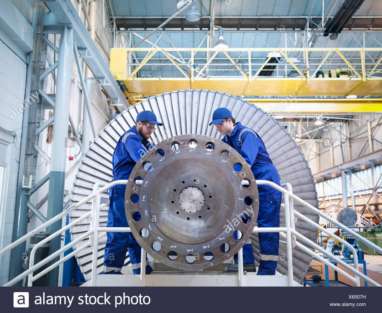 Engineers repairing steam turbine in workshop - Stock Image