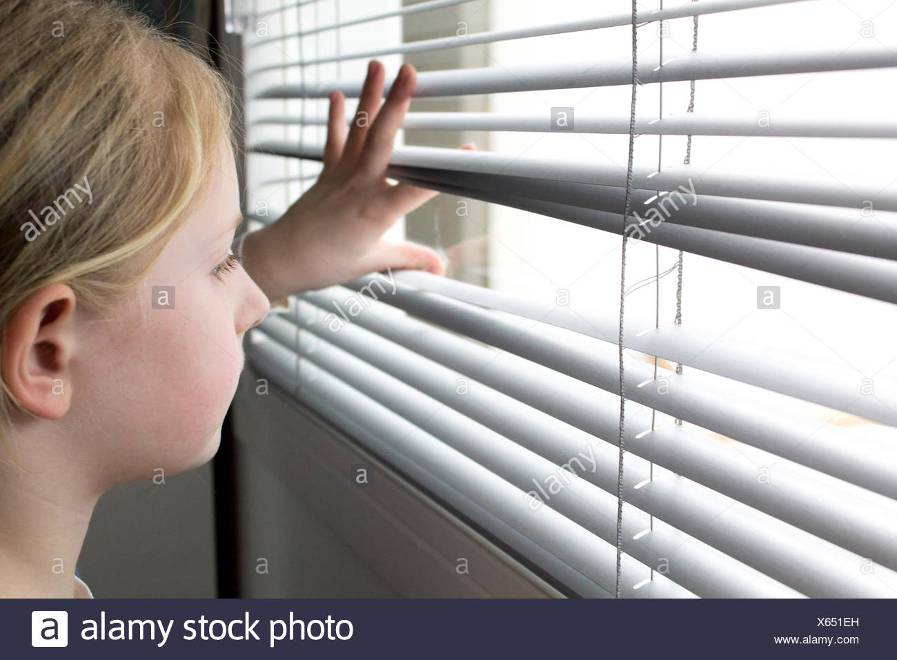 Girl looking through window blinds - Stock Image