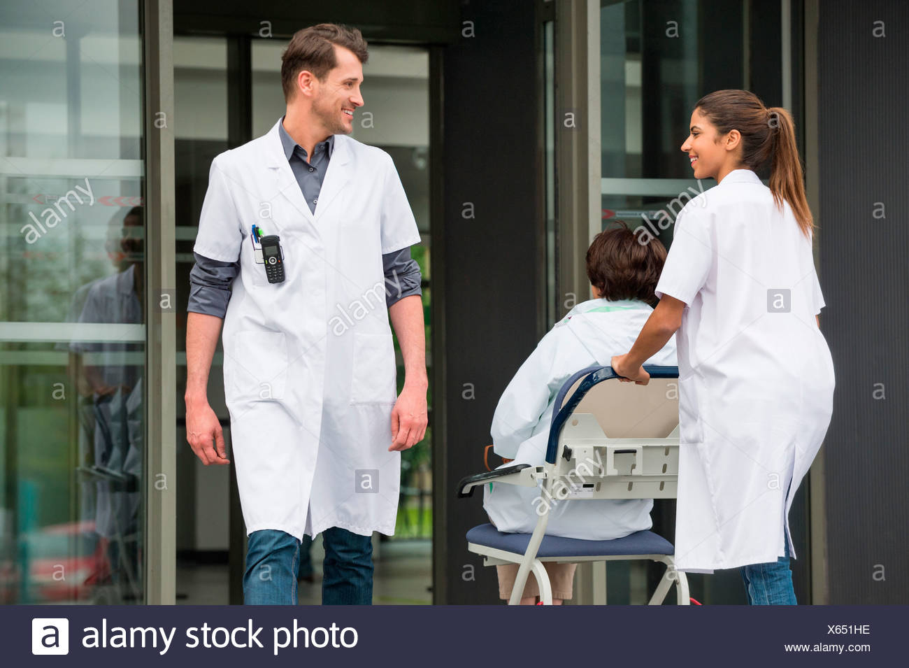 Female doctor pushing a patient on chair while looking at a male doctor - Stock Image