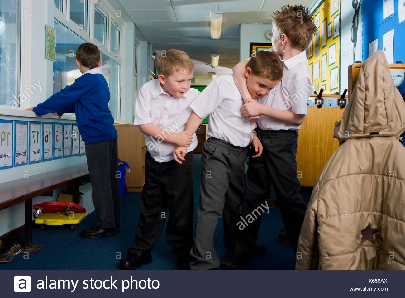 Aggressive school boys rough housing in classroom - Stock Image